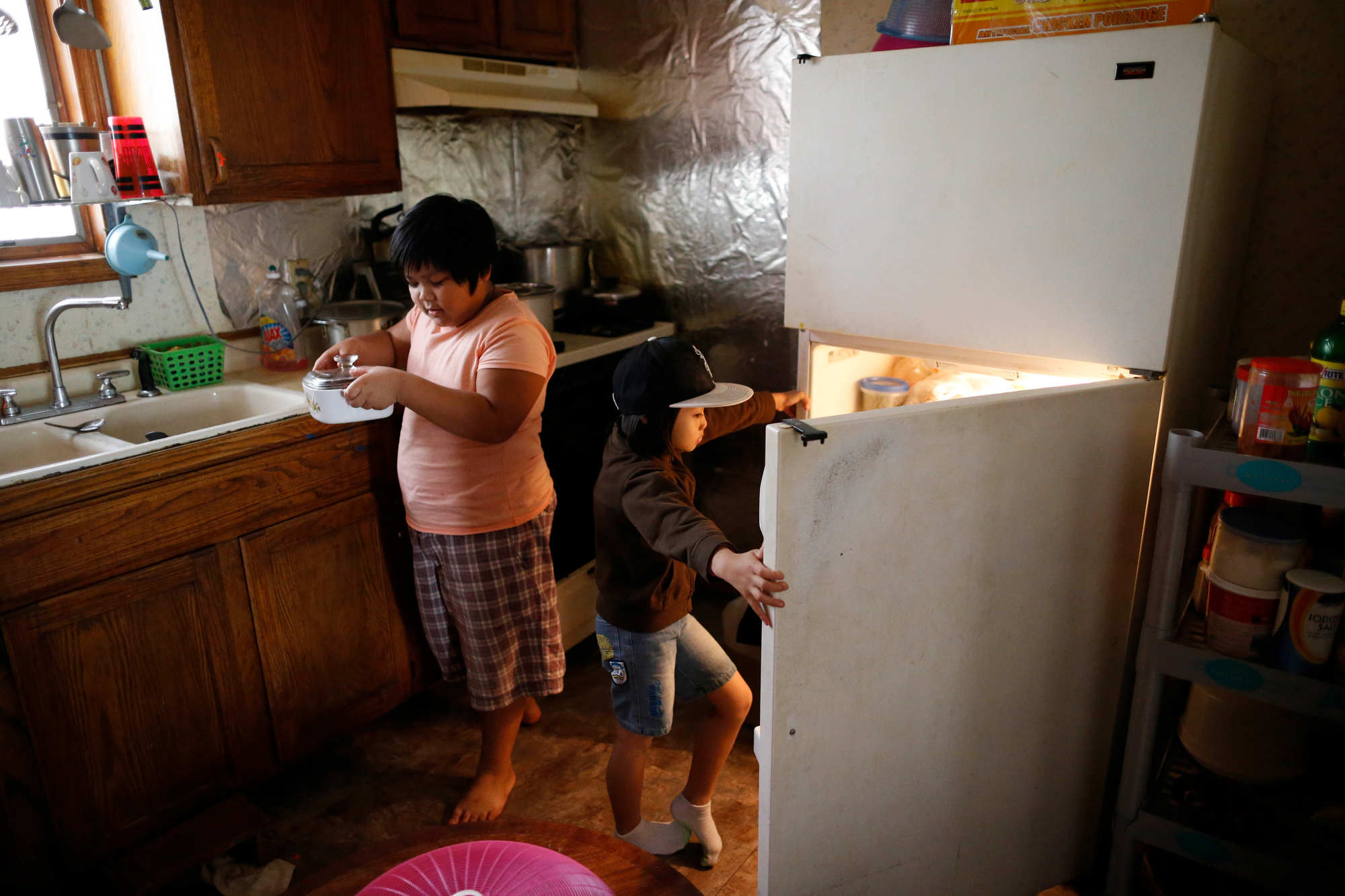 Pra Ah, 9, and Paw Eh Lar Say, 5, children of Htay Beh, a refugee from Burma, help themselves to food in the kitchen of their Riverside home on Nov. 15, 2015. (Derek Gee/Buffalo News)