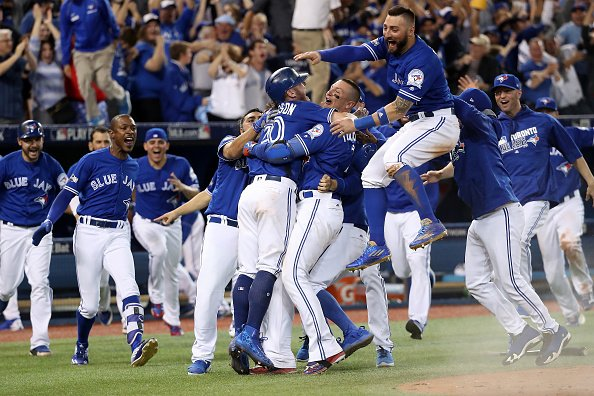 Josh Donaldson is mobbed by his teammates after scoring the ALDS-winning run against the Rangers (Getty Images).
