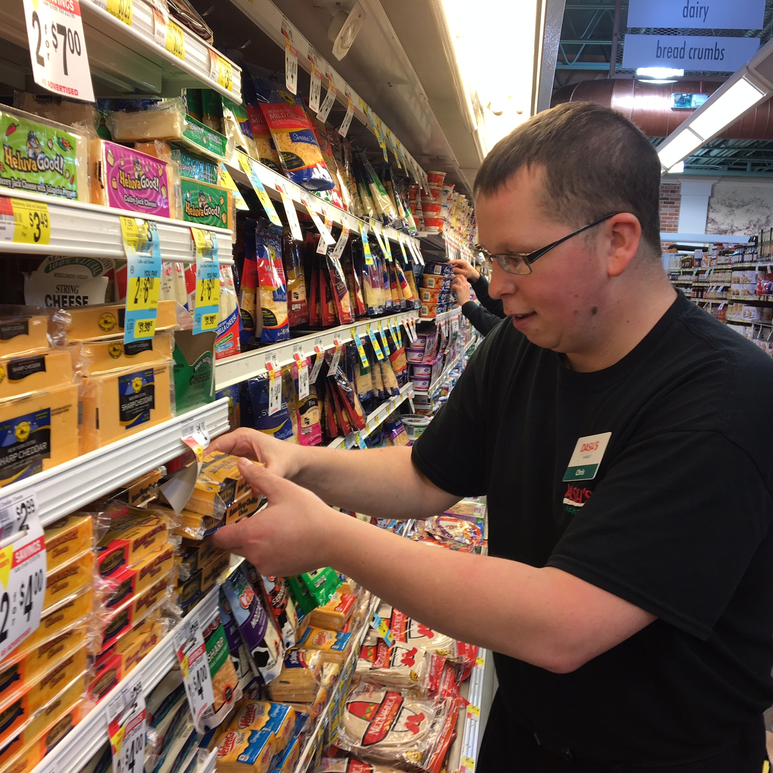 Chris Taverna pushes product up to the front of the shelves in both the dairy and frozen food sections at Dash's Market in Clarence. (Photos by Scott Scanlon/Buffalo News)