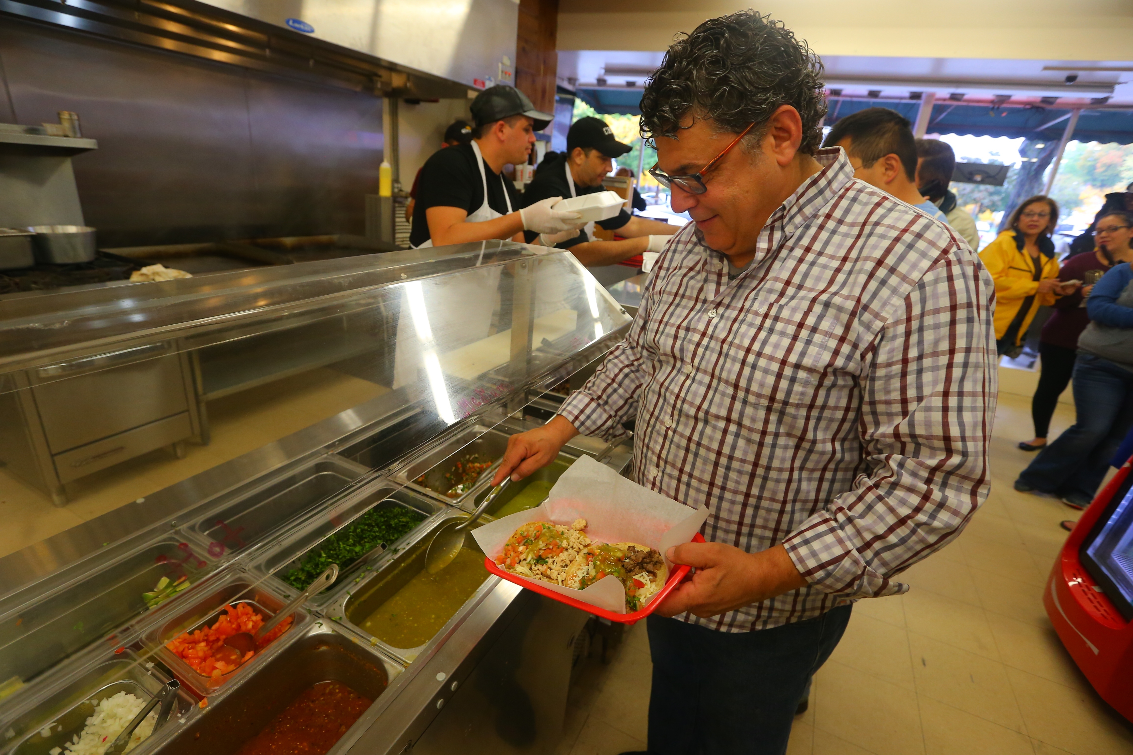 George Dolce of Kenmore with his taco's at La Divina Mexican Store on Friday Oct. 21, 2016, La Divina Mexican Store reopened after briefly closing following a raid by federal agents and the arrest of Sergio Mucino and several employees, in Kenmore, N.Y., earlier this week. (John Hickey/Buffalo News)
