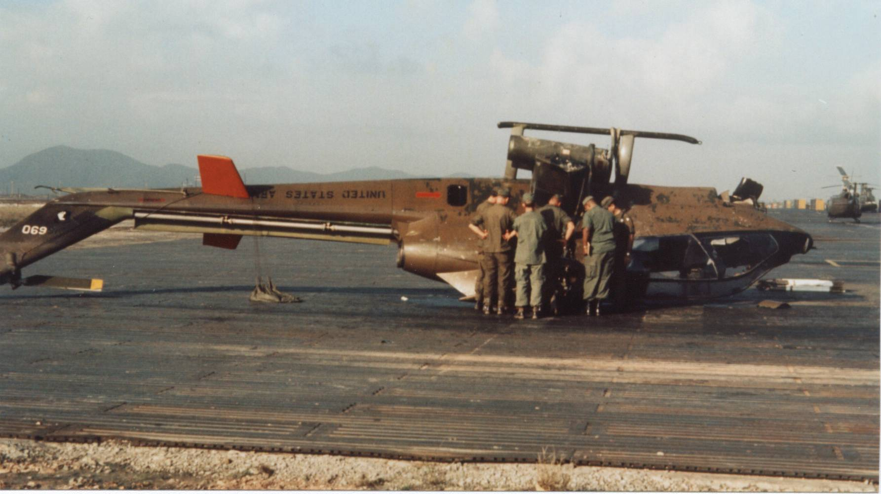 Army helicopter maintenance workers and crew chiefs remove rockets and fuel from a Cobra attack helicopter on Jan. 20, 1972 in Phu Bai, Vietnam. The helicopter, piloted by Jimmie D. Ferguson and Mike Neufeld, had been shot down a day earlier. This helicopter is set to become the centerpiece of a new Vietnam veterans memorial in the City of Tonawanda. Photo courtesy of Jimmie D. Ferguson.