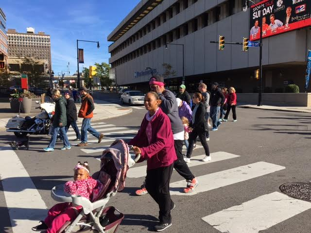 Making Strides Walk participants stroll past The Buffalo News building near Canalside.