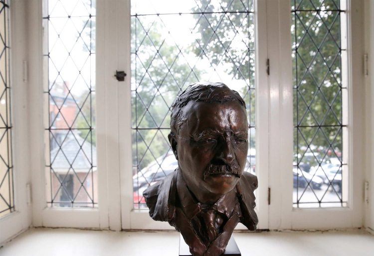 A bust of Theodore Roosevelt sits in a leaded glass window that is original to the 1896 addition to the Wilcox Mansion. Roosevelt was just 42 when he took the oath of office in the suit and long coat he would later wear in President William McKinley's funeral procession. (Derek Gee/Buffalo News)