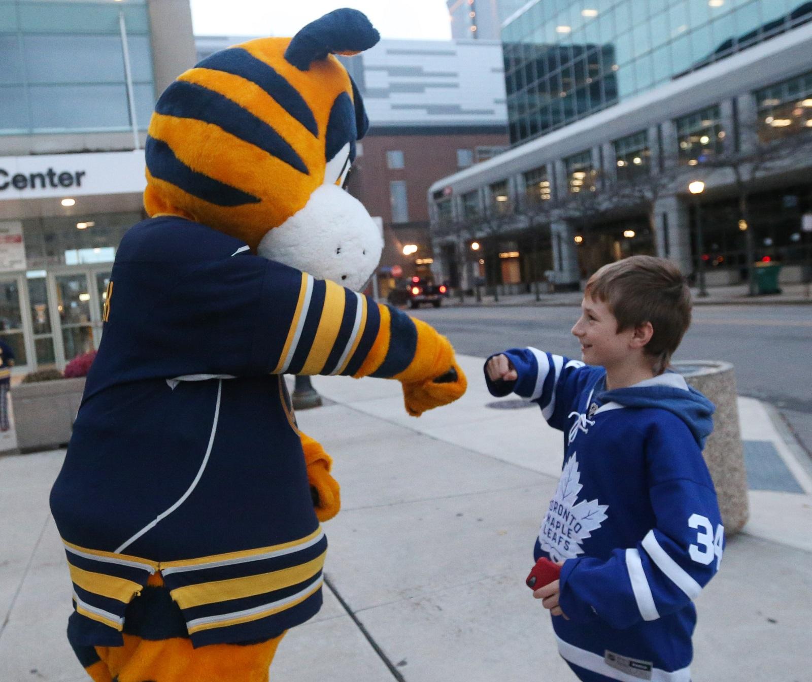 Sabres mascot Sabretooth greets young Leafs fan Brandon Fishman, 9, of Waterloo, Ontario. (Sharon Cantillon/Buffalo News)