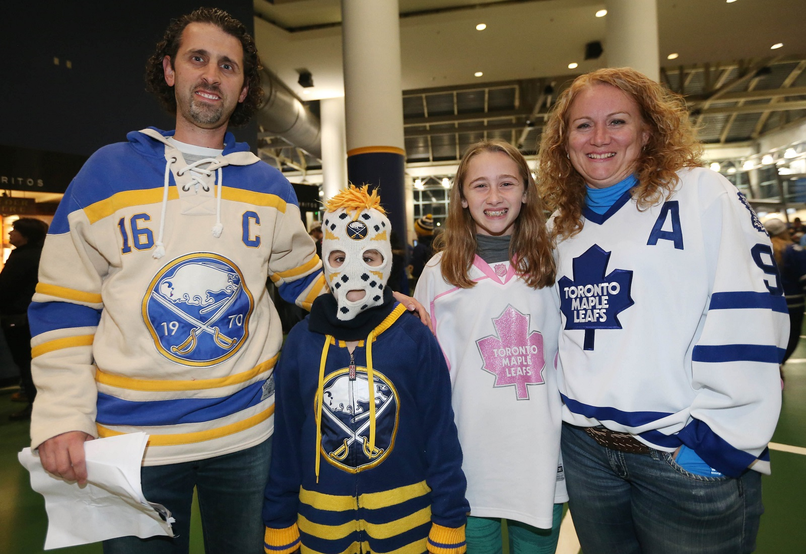 A family from St. Catharines, Ontario, with split allegiances arrives at the game. From left are Sabres fans Mark and daughter Kayleigh Digirola, and Leafs fans Gabriella and her mother Allison Digirola. (Sharon Cantillon/Buffalo News)
