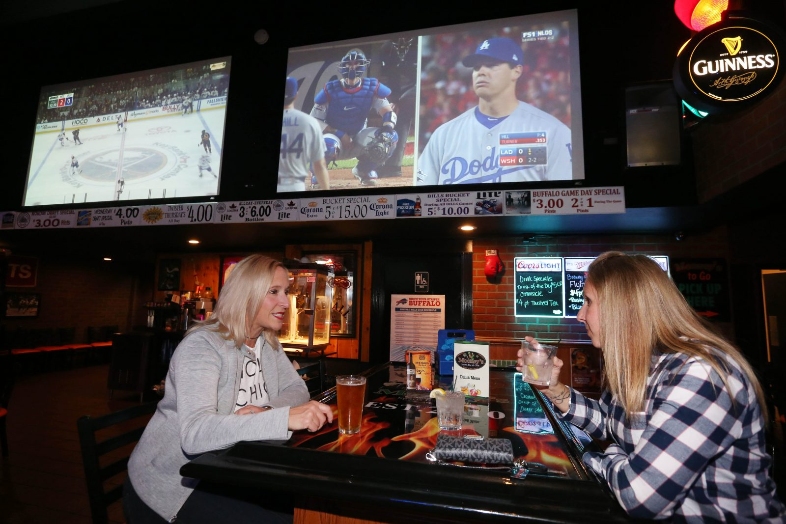 Two large-screen televisions tower above Marie Burzynski, left, and Brandy Mroz, of West Seneca, at Mooney's in West Seneca. (Sharon Cantillon/Buffalo News)