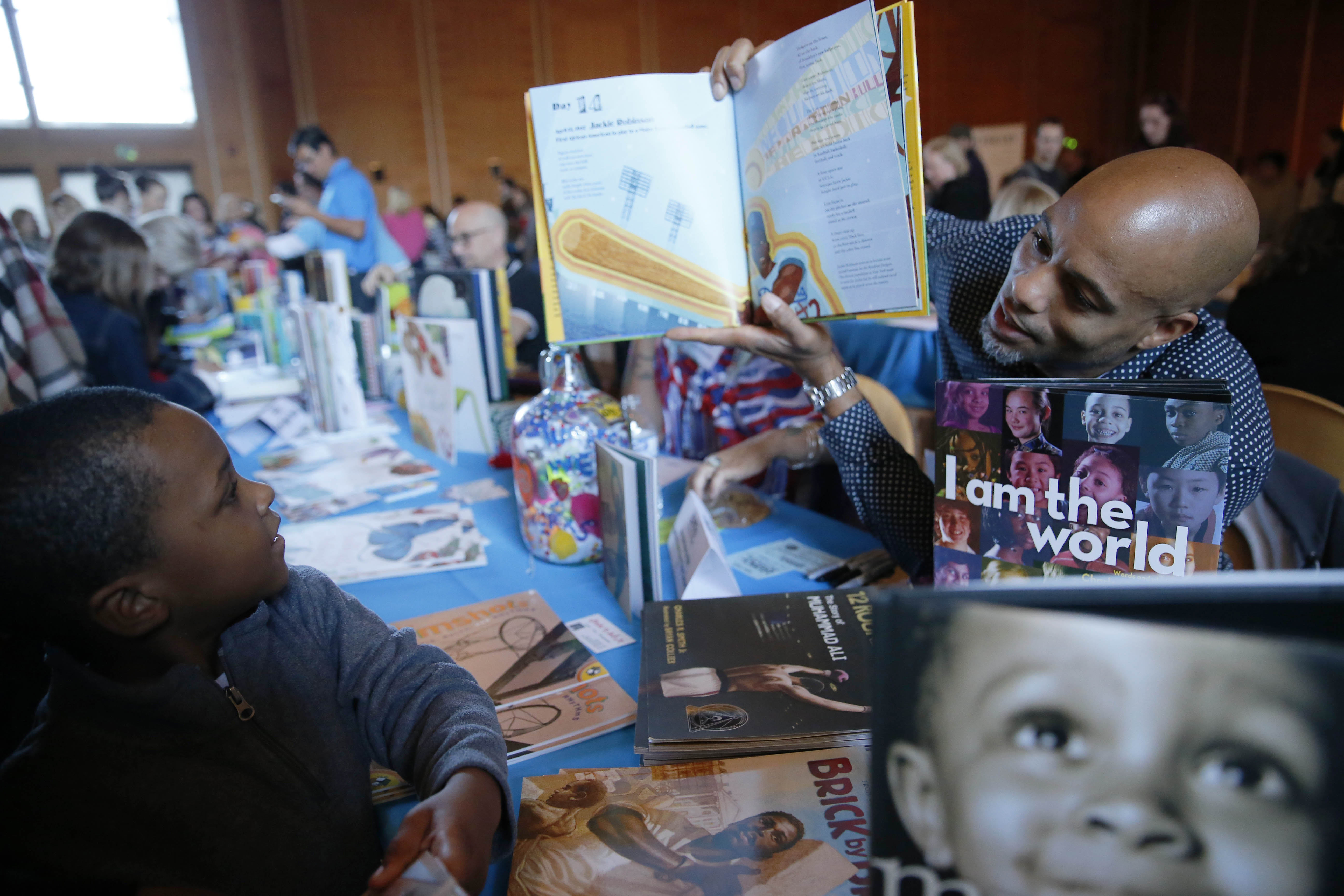"""Author Charles R. Smith Jr. holds up a copy of his book """"28 Days: Moments in Black History that Changed the World"""" while telling young Joshua Bell, 4, of Buffalo, about baseball player Hank Aaron at the WNY Children's Book Expo at Kleinhans. (Derek Gee/Buffalo News)"""