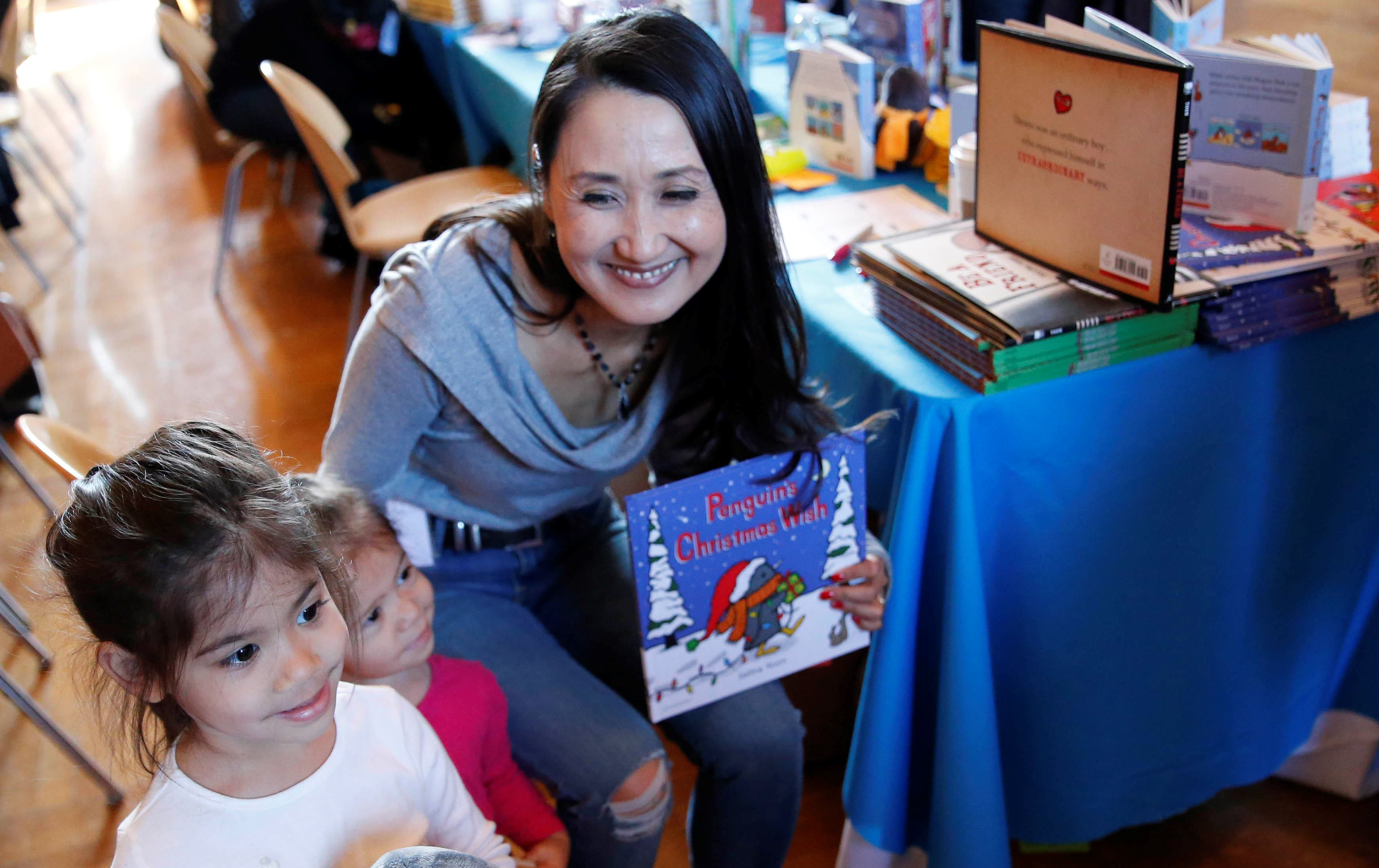 Sisters Rosalie and Hazel Htun, ages 4 and 2, pose for a photo with author Salina Yoon of San Diego and the penguin character from her book at the WNY Children's Book Expo at Kleinhans on Sunday, Nov. 6, 2016. (Derek Gee/Buffalo News)