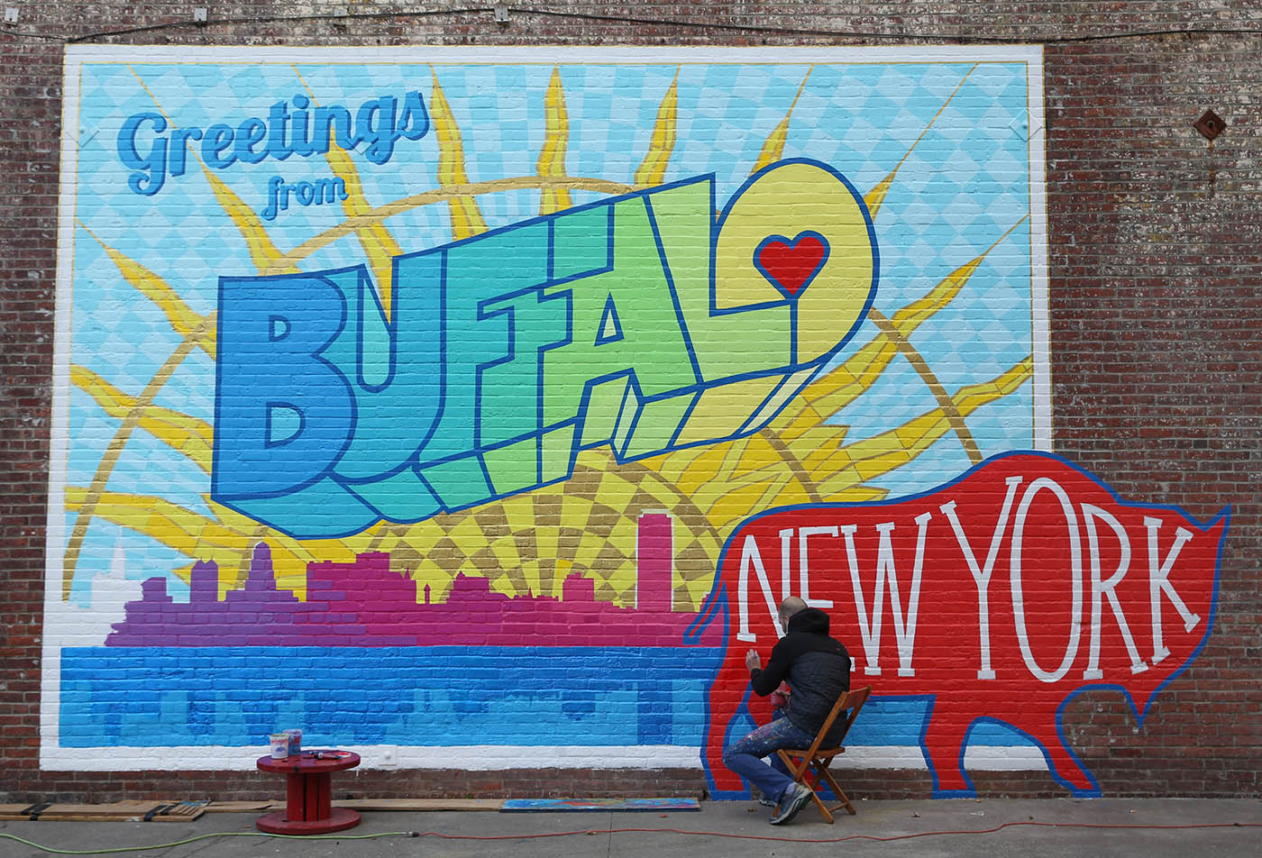 Artist Casey William Milbrand works on his colorful new 'Greetings from Buffalo' mural on the south side of the Washington Market building at 461 Ellicott St,, Tuesday, Oct. 25, 2016.  (Sharon Cantillon/Buffalo News)