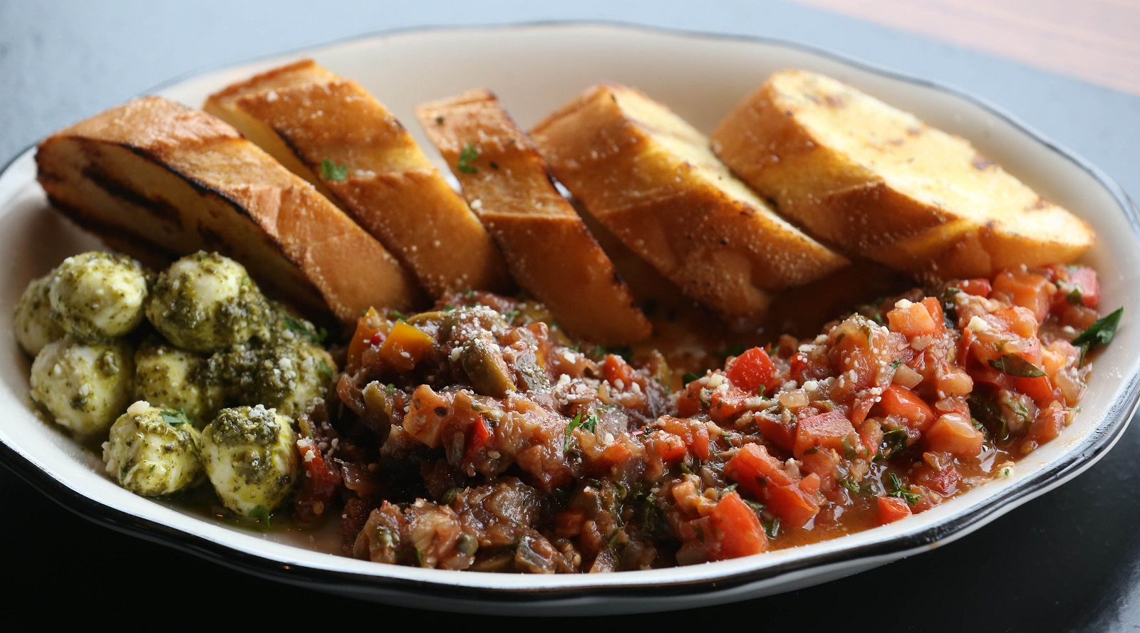 Giacobbi's Cucina Citta's bruschetta trio includes Ciliegine pesto, caponata and bruschetta tomatoes with grilled Italian bread and fresh grated romano. (Sharon Cantillon/Buffalo News)