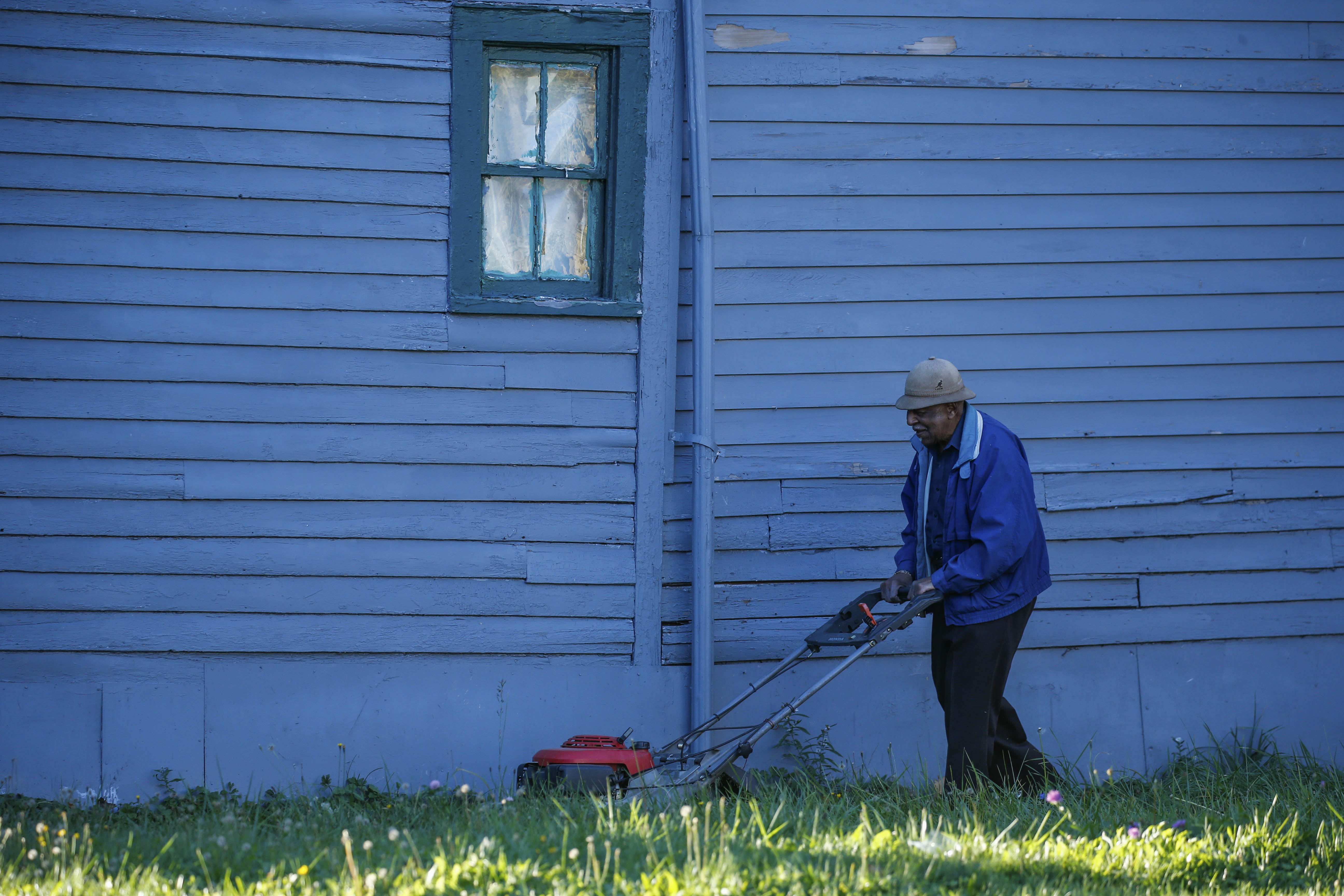 Henry Boyd takes advantage of a pleasant, 63-degree day on Nov. 7 to mow his lawn on Dodge Street in Buffalo.  (Derek Gee/Buffalo News)