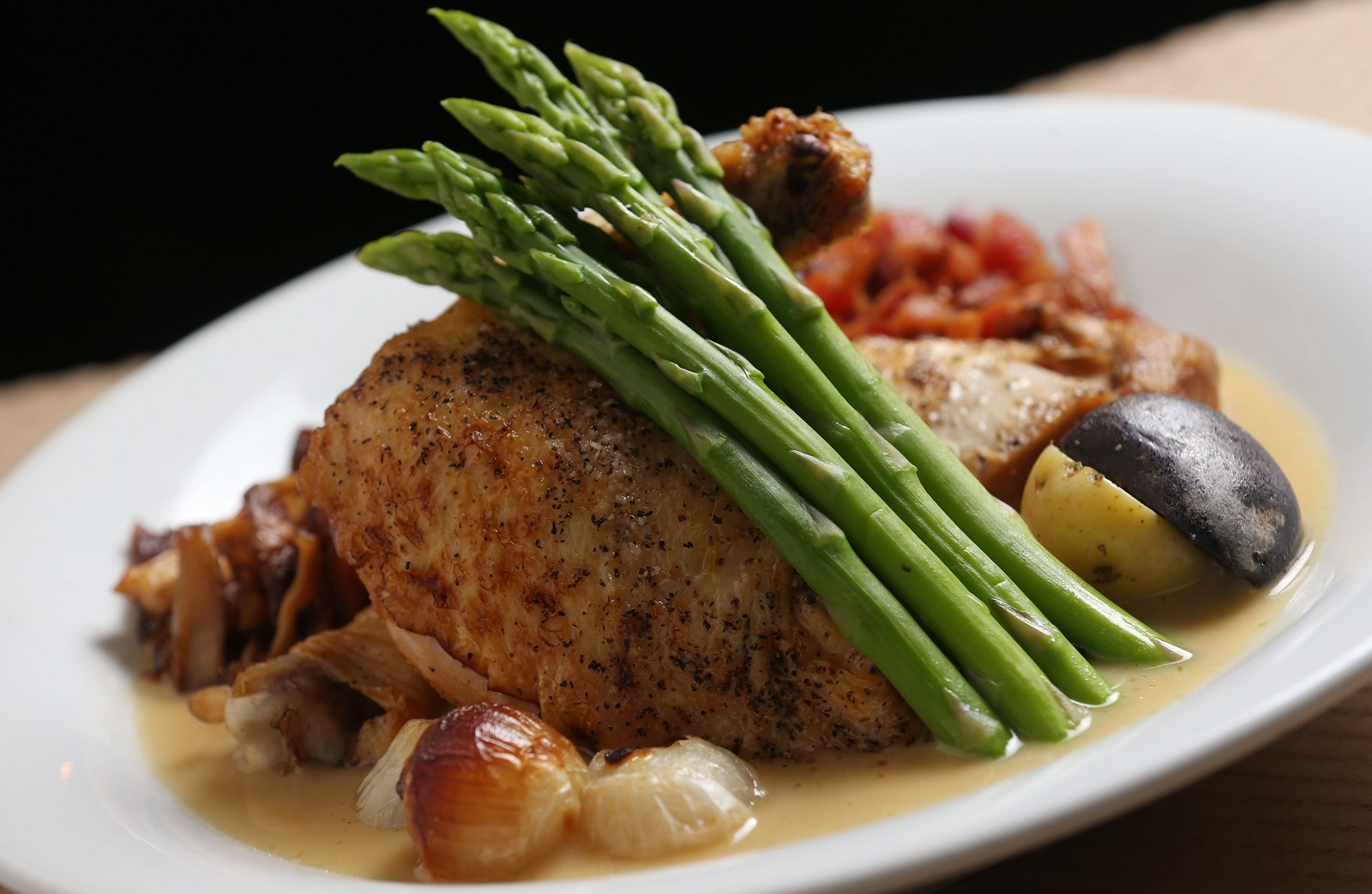 Coco's Poulet Grand-mere is prepared with braised bone-in chicken, caramelized mushrooms, whole roasted garlic, pearl onions, lardons, potatoes and asparagus. (Sharon Cantillon/Buffalo News)