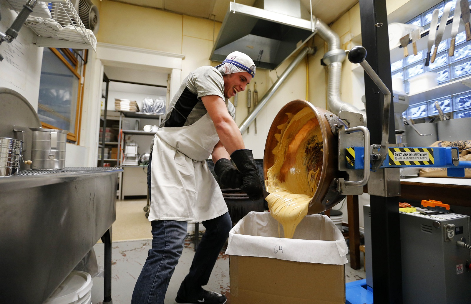 Vinny Libroia pours out the sponge candy mixture at Ko-Ed Candies in South Buffalo. (Mark Mulville/Buffalo News)