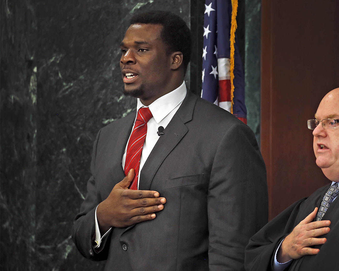 Cyrus Kouandijo, left, a Buffalo Bills lineman and a native of Cameron, Africa, leads the Pledge of Allegiance, with Judge Michael J. Roemer during a naturalization ceremony at the courthouse in Buffalo on Thursday, Nov. 17, 2016. (Robert Kirkham/Buffalo News)