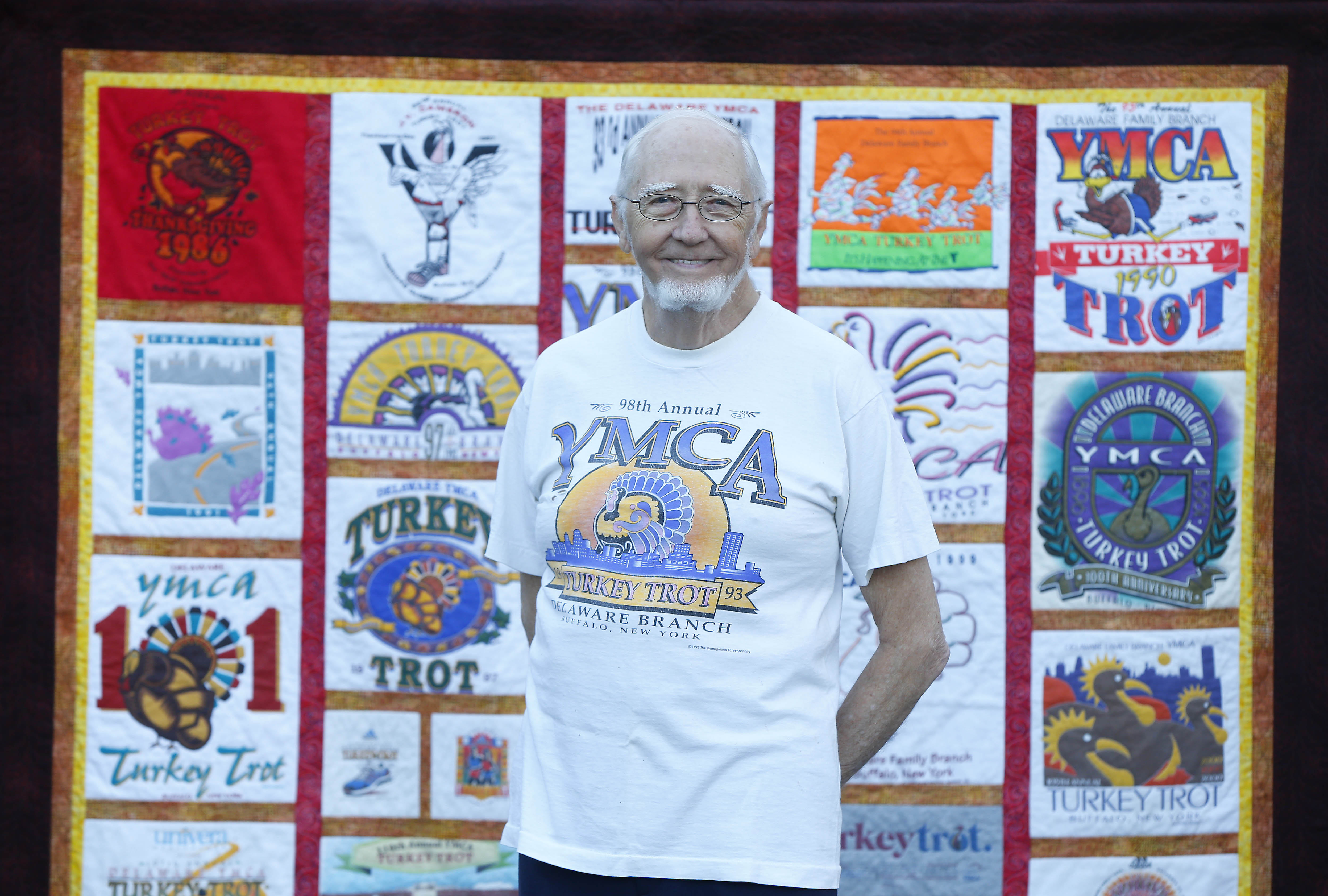 Mike Moran stands with the quilt he had made from his Turkey Trot shirts at his home in Amherst (Mark Mulville/Buffalo News)