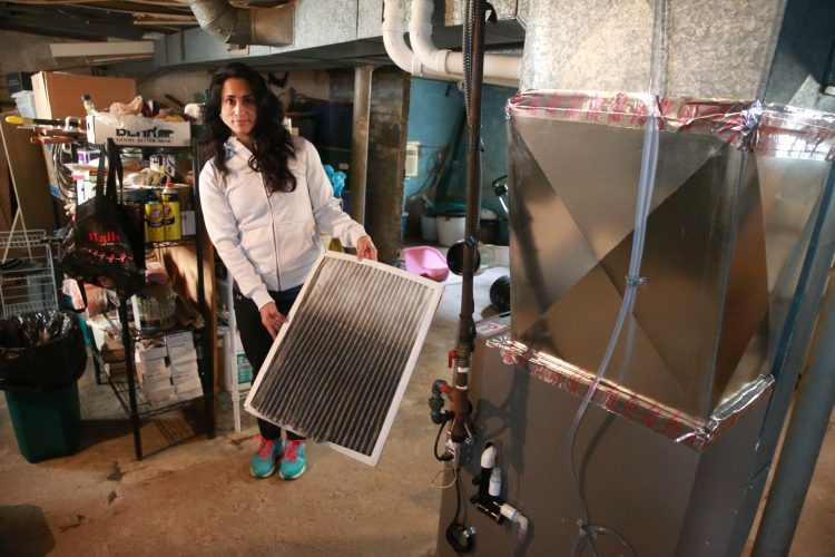 Amy Claroni holds her furnace filter filled with black soot after changing it last Saturday. Claroni, the daughter of a former steelworker, has been researching some of the chemicals, and materials released by a fire at the former Bethlehem Steel plant, and worries that they may have an impact on her and her neighbors health at her home in Bethlehem Park. (John Hickey/Buffalo News)