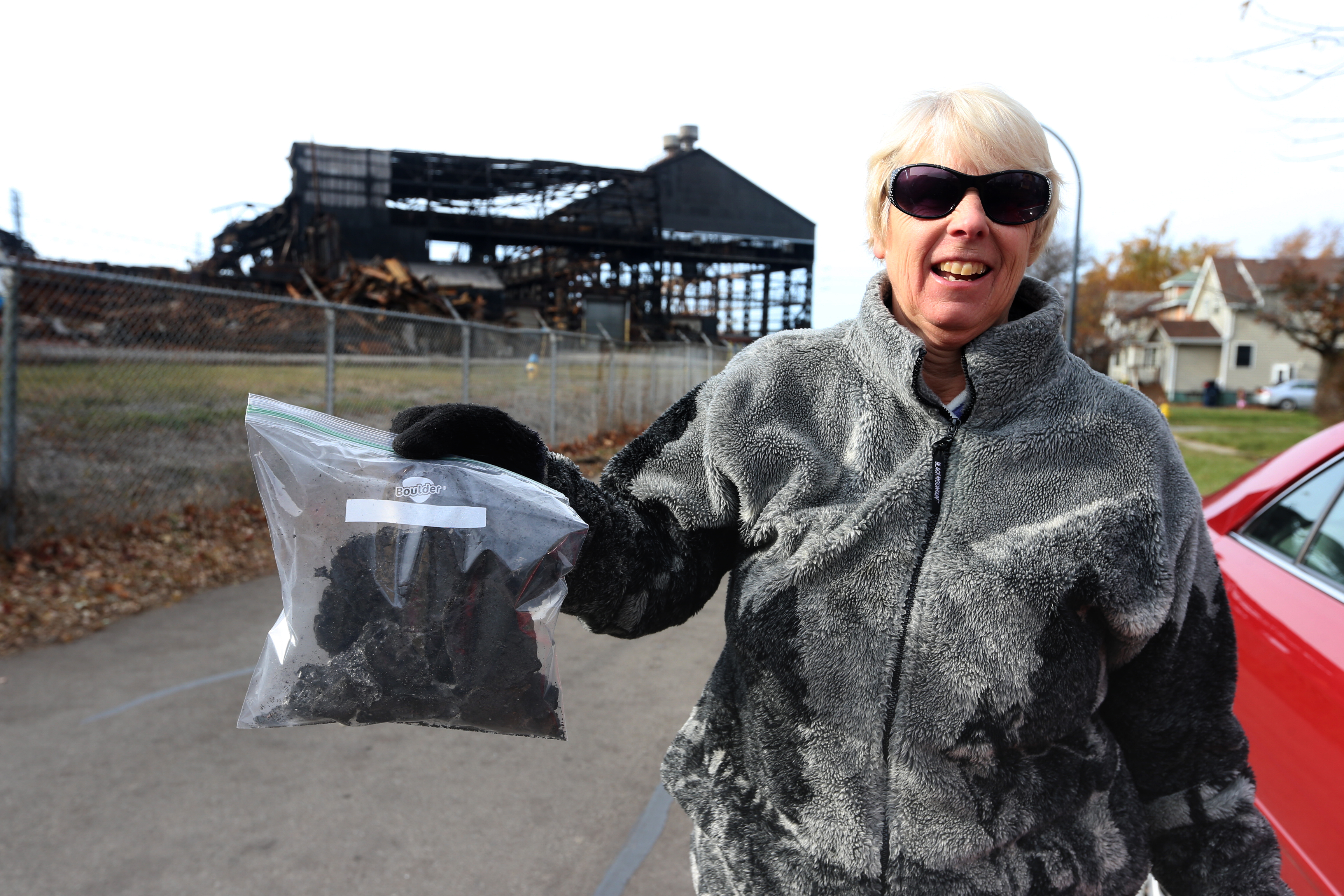 Eileen Wahl of Hamburg, N.Y. who lives about 4 miles from the former Bethlehem Steel Plant , in Lackawanna, N.Y., on Wednesday, Nov. 23, 2016 shows off charred debris she bagged that landed in her yard. (John Hickey/Buffalo News)