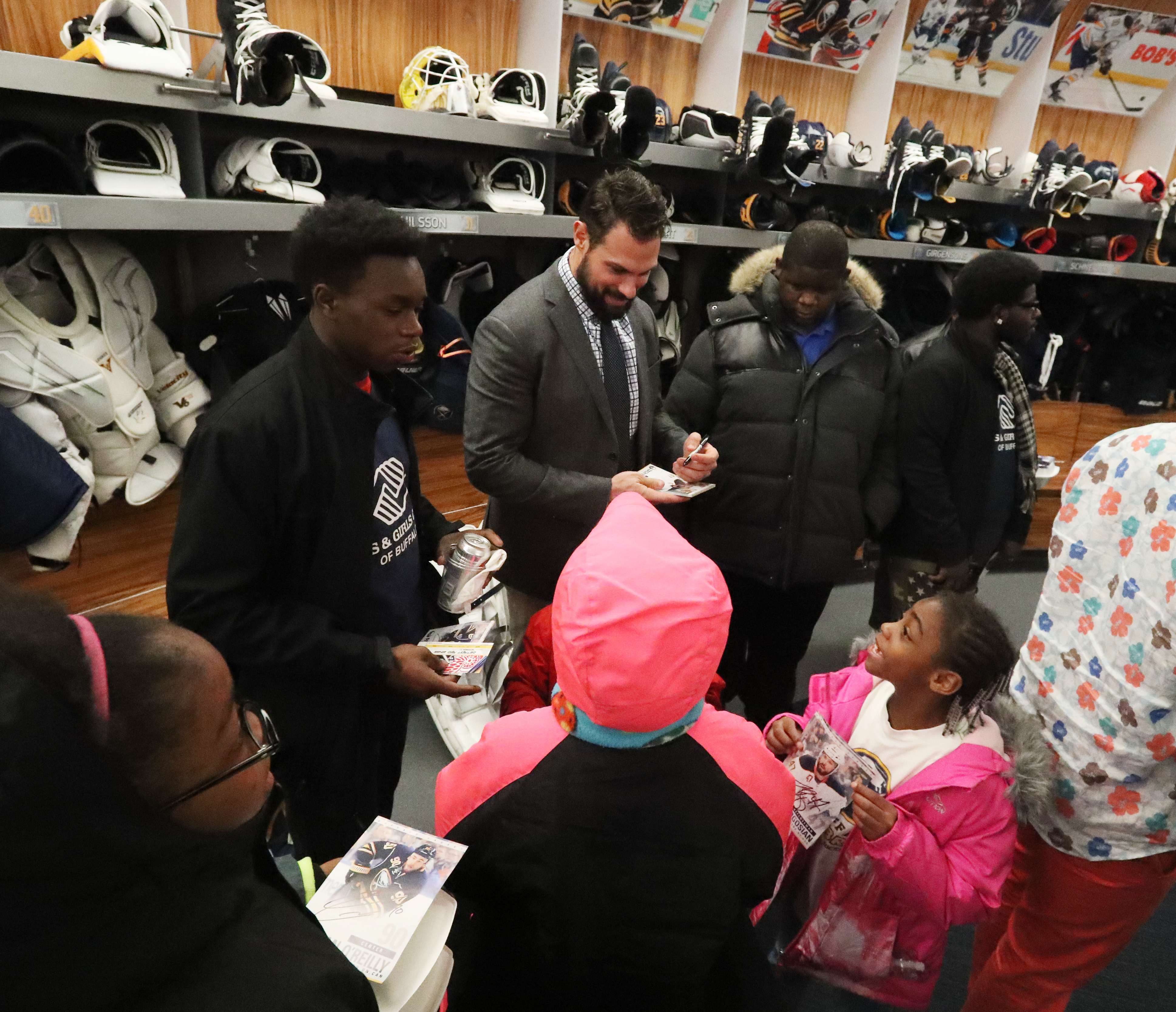 Zach Bogosian, who along with Ryan O'Reilly purchased a KeyBank Center suite to donate to charity, meets with kids in the locker room after Wednesday's game against the Red Wings. (James P. McCoy/Buffalo News)