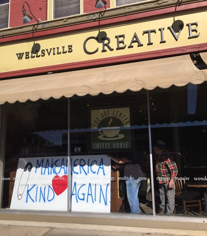 """A """"Make America Kind Again"""" sign hands from the window of the Wellsville Creative Arts Center. (David Fredrickson)"""