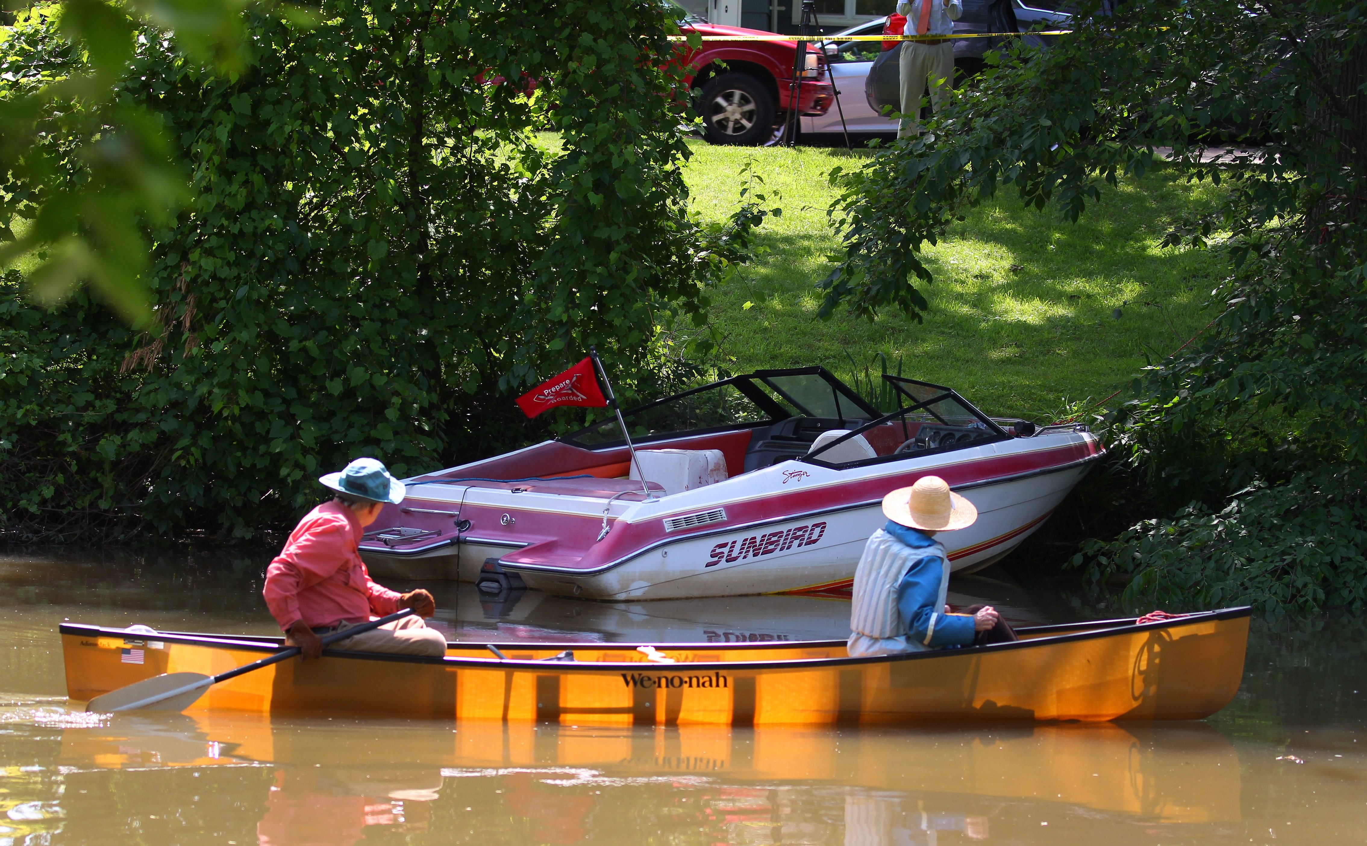 A couple paddles past the boat that was involved in an accident resulting in the death of 16-year-old Avery Gardner on Ellicott Creek in Tonawanda in 2015. (Mark Mulville/News file photo)