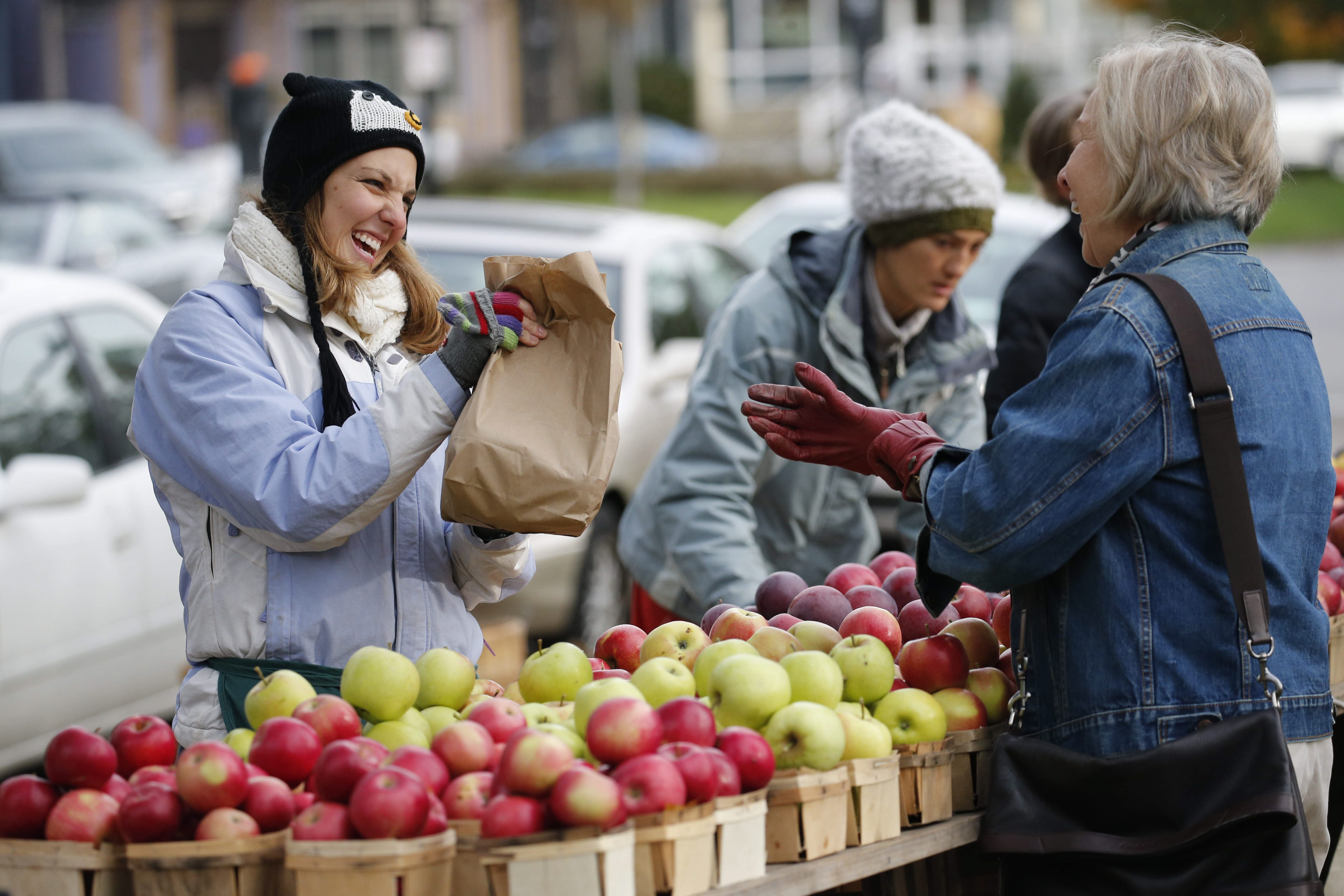 A customer purchases apples at the Tom Tower Farm stand at the Elmwood-Bidwell Farmers Market. (Derek Gee/Buffalo News)