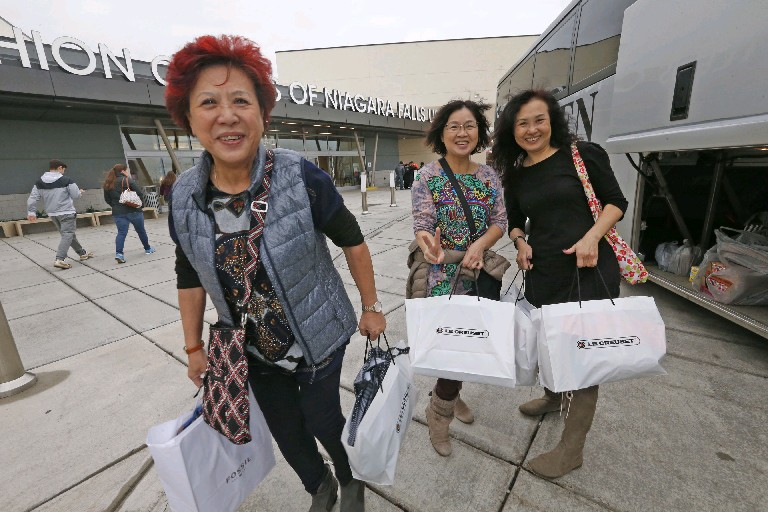 From left, Lucia Chan, May Kong and Shirley Luk, all of Toronto, walk back to their chartered tour bus with bags of gifts from the Fashion Outlets of Niagara Falls after a long day of shopping Friday. (Robert Kirkham/Buffalo News)