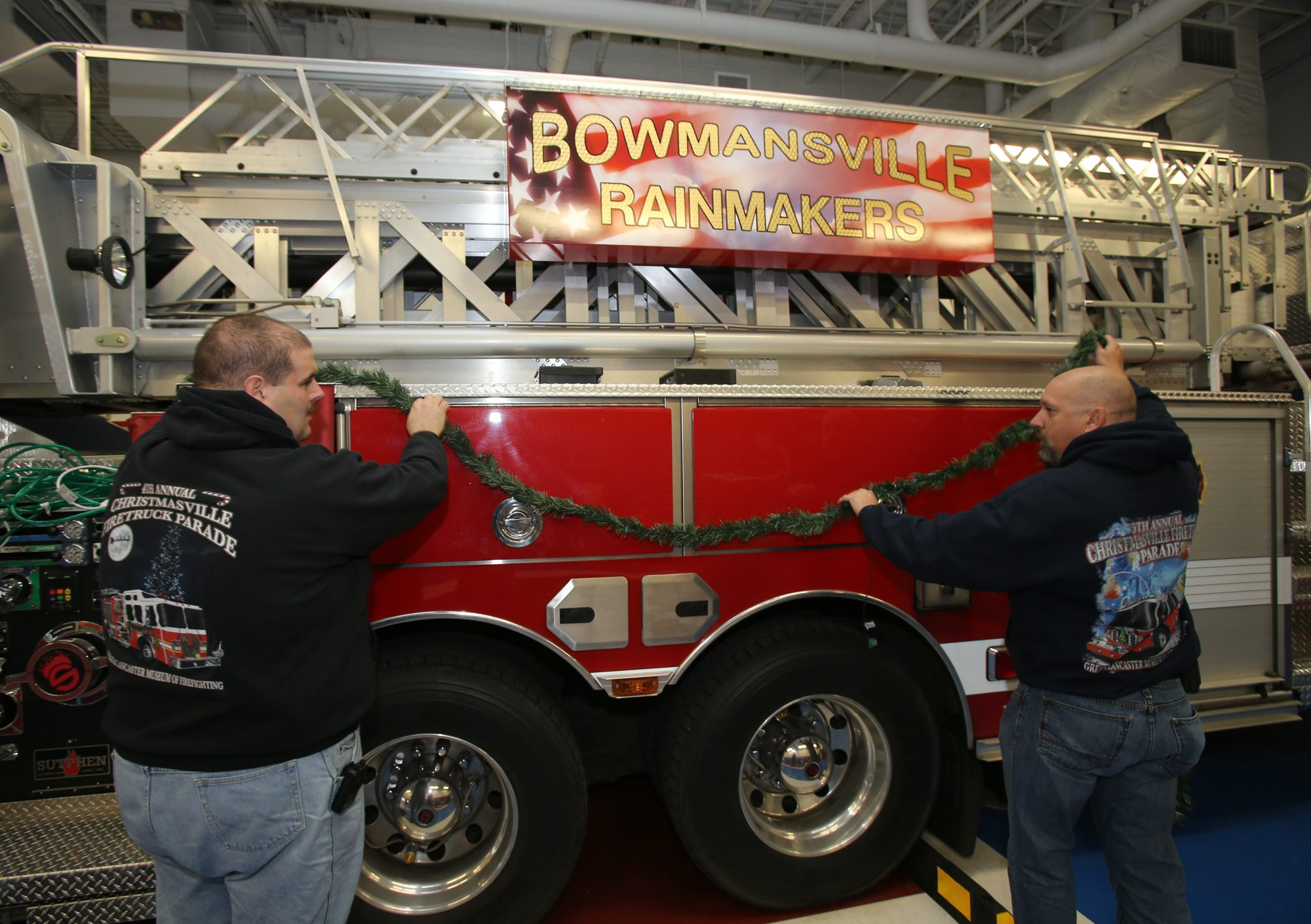Tom Trzepacz, left, and Jerry Enser, co-chairs of the Christmasville Fire Truck Parade in Lancaster,  decorate a ladder truck at the Bowmansville Fire Station on Nov. 21, 2013.  (File photo by Charles Lewis / Buffalo News)