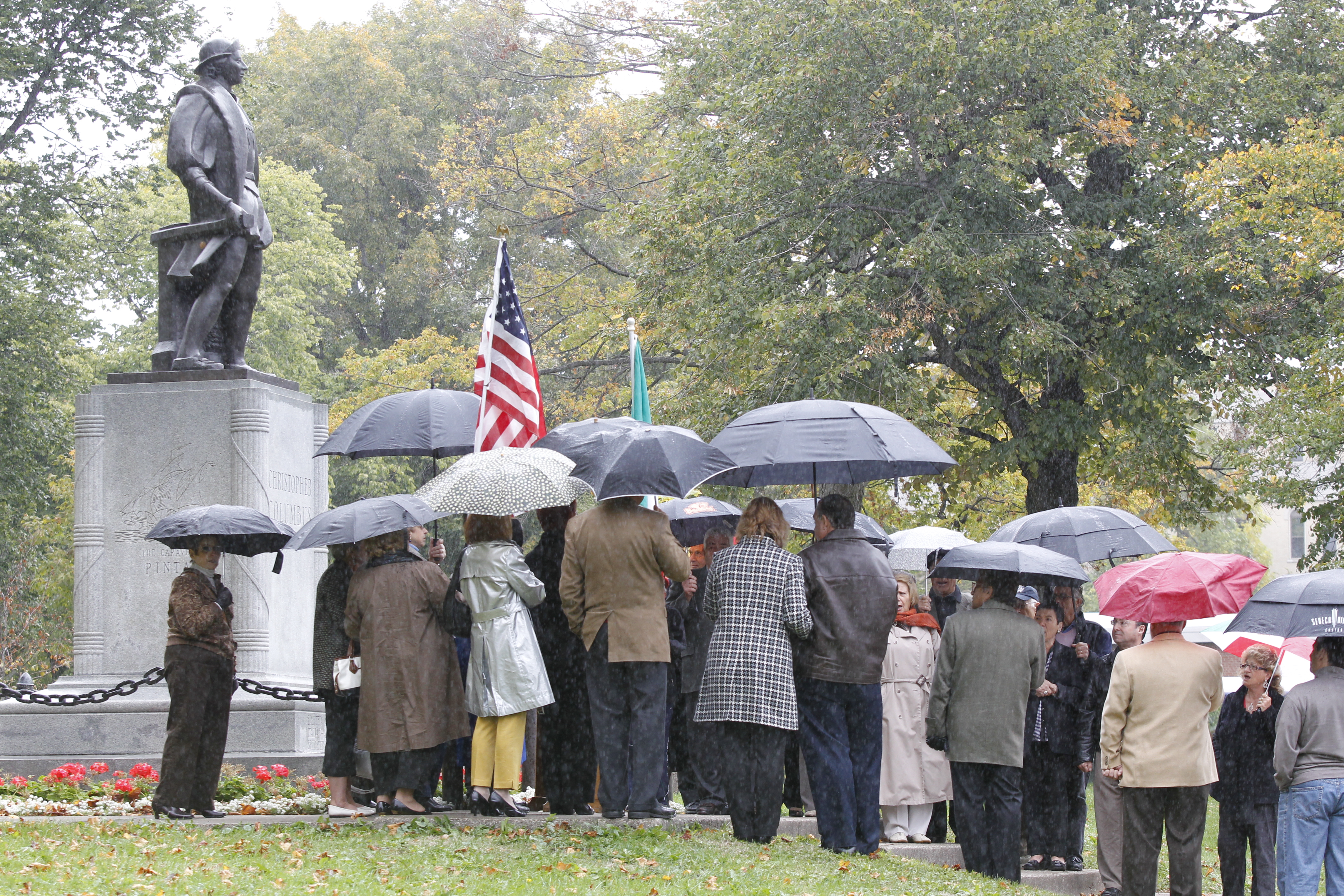Members of the Italian American Societies of Western New York mark a rainy Columbus Day in 2012 at the Christopher Columbus statue in Prospect Park.  (Photo by Harry Scull Jr./Buffalo News)