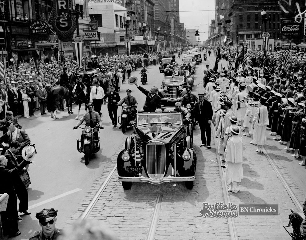 Alfred Landon waves his hat to Buffalonians lined up in Shelton Square and along Main Street in August, 1936. Today, this spot has One M&T Plaza to the left, and the Main Place Tower and Mall to the right.