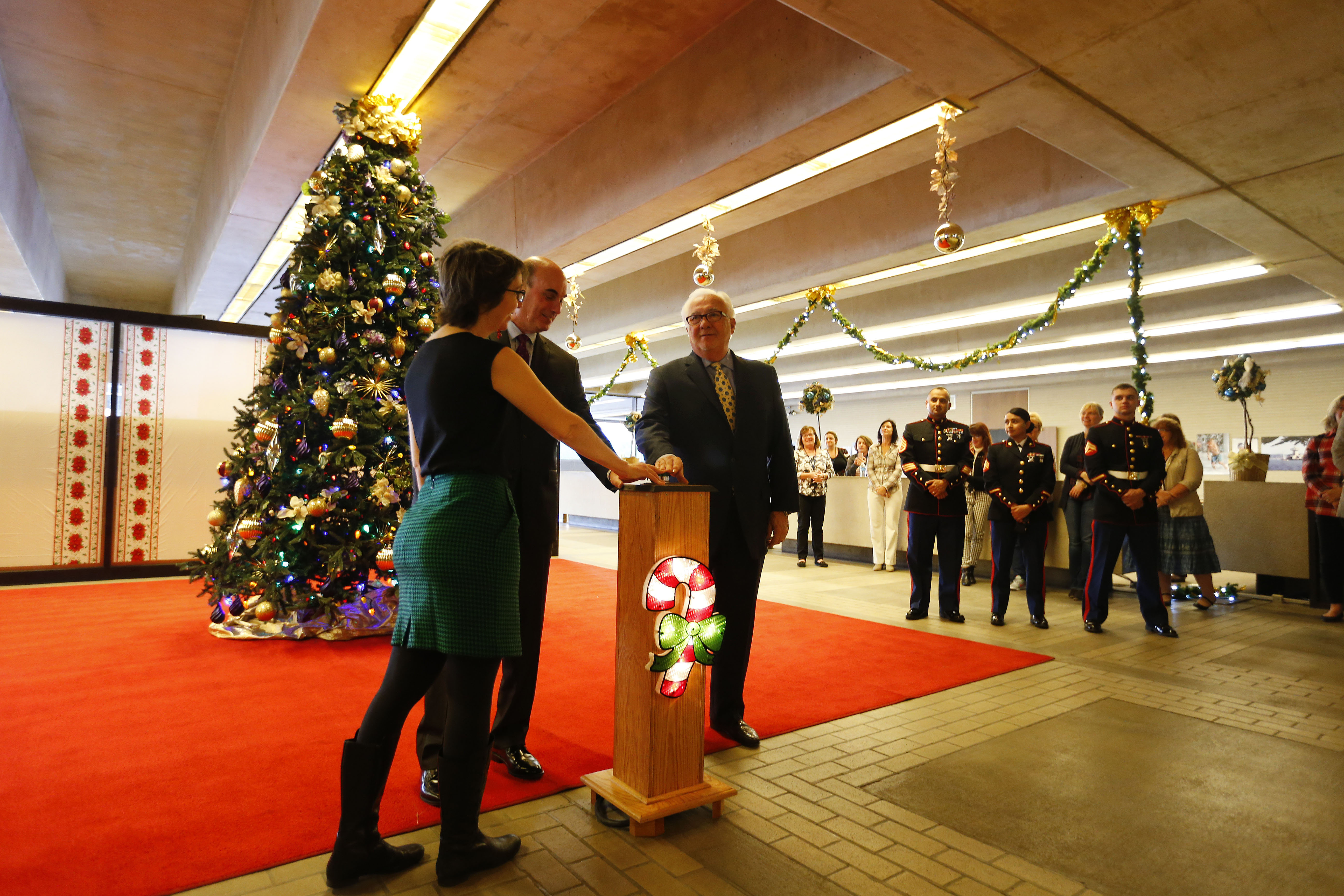 Buffalo News Publisher Warren Colville, right, United Way of Buffalo & Erie County President and CEO Michael Weiner, center, and Olmstead Center for Sight's Kelly Dodd, left, light the Christmas tree kicking off the News Neediest program in the lobby at The Buffalo News in Buffalo Friday, Nov. 18, 2016. (Mark Mulville/The Buffalo News)