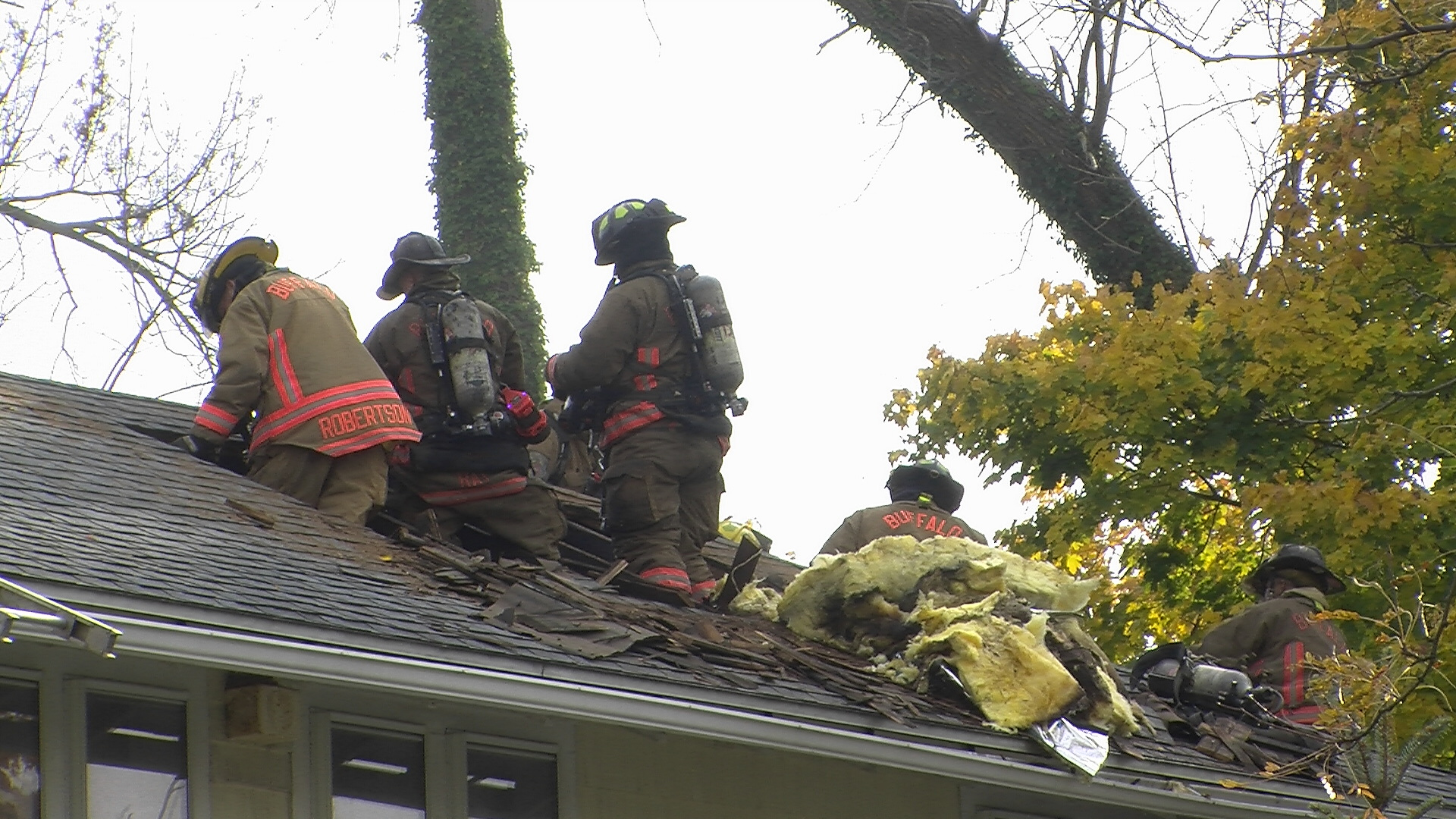 Buffalo firefighters cut the roof of a home on Tillinghast Place in North Buffalo. Photo by Joseph Popiolkowski / Buffalo News.