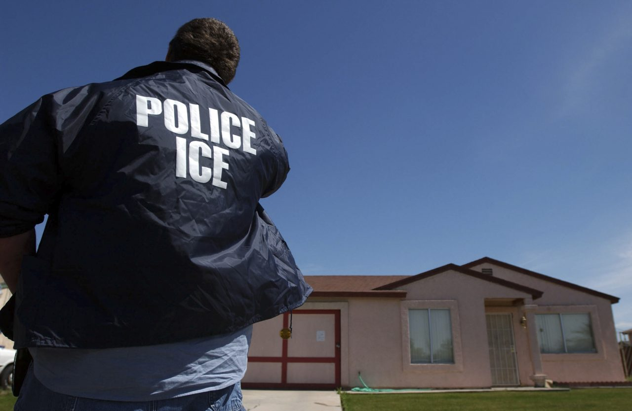 An Immigration and Customs Enforcement agent outside a home in California.  (Ann Johansson/The New York Times)
