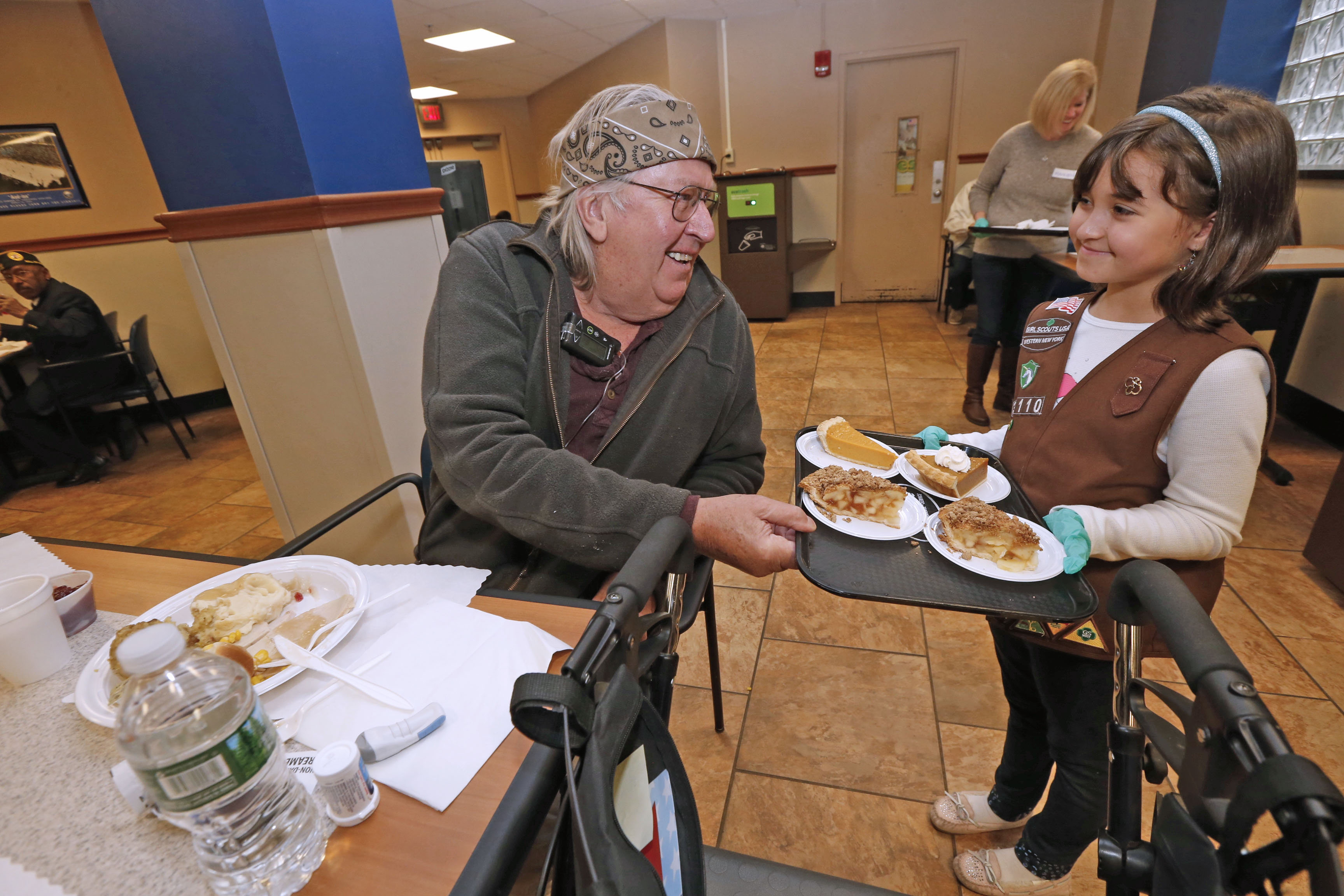 Girl Scout Brownie Sophia Pawlukovich, of Troop 31110, offers Vietnam war veteran Gerald Carrigan of Clarence some pie to go, along with his Thanksgiving dinner in the Patriot Cafe at the Buffalo VA Medical Center Sunday. (Robert Kirkham/Buffalo News)