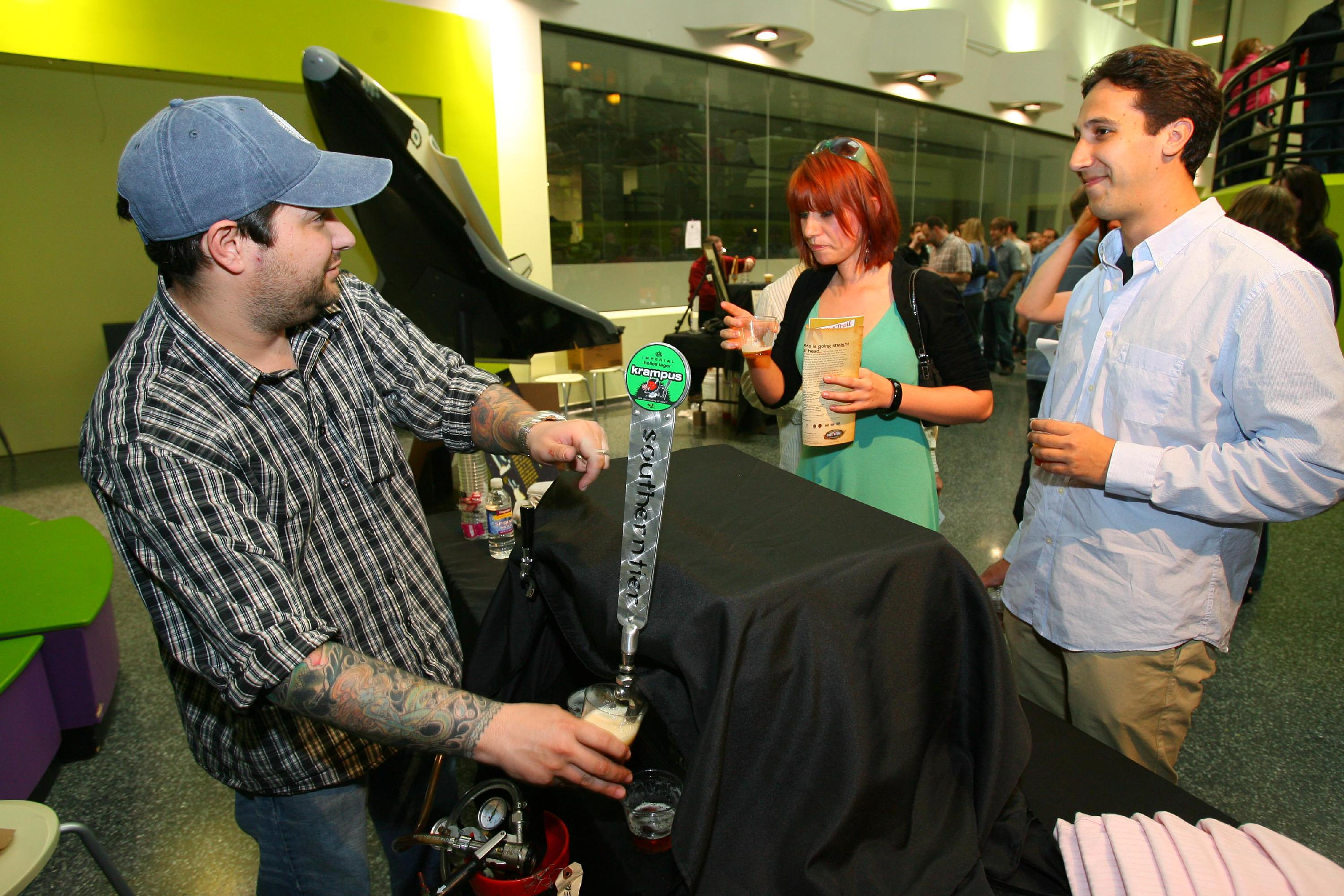 Brian Nelson, left, pours a Krampus Helles Lager from Southern Tier Brewery for Lindsey Jakiel and Adam Diulus, both of Amherst, during a previous Beerology at the Buffalo Museum of Science. (Buffalo News file photo)