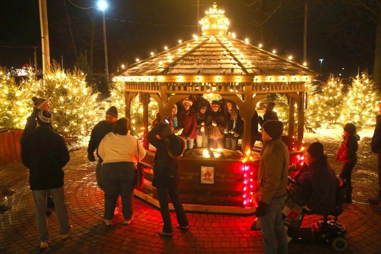 People enjoy a fire pit at the Festival of Lights. (Robert Kirkham/Buffalo News)