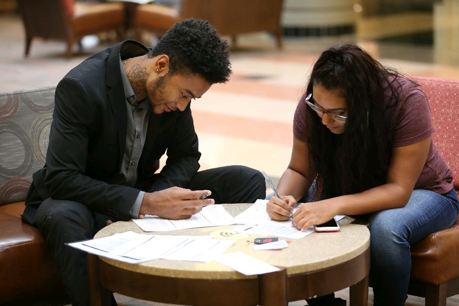 Caleb Sanchez, left, and Maribel Rivera fill out applications at the Walden Galleria, which held a job fair to hire temporary seasonal workers. (Sharon Cantillon/ Buffalo News)