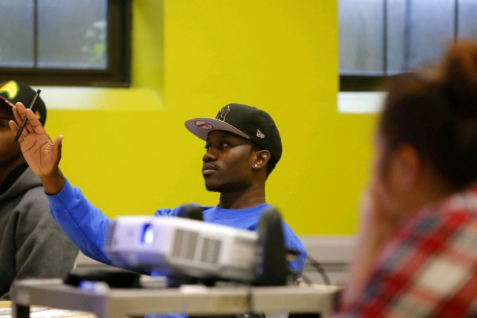 Felix Madji raises his hand to ask a question during an economics class at Houghton College at the First Presbyterian Church in Buffalo. (Mark Mulville/Buffalo News)
