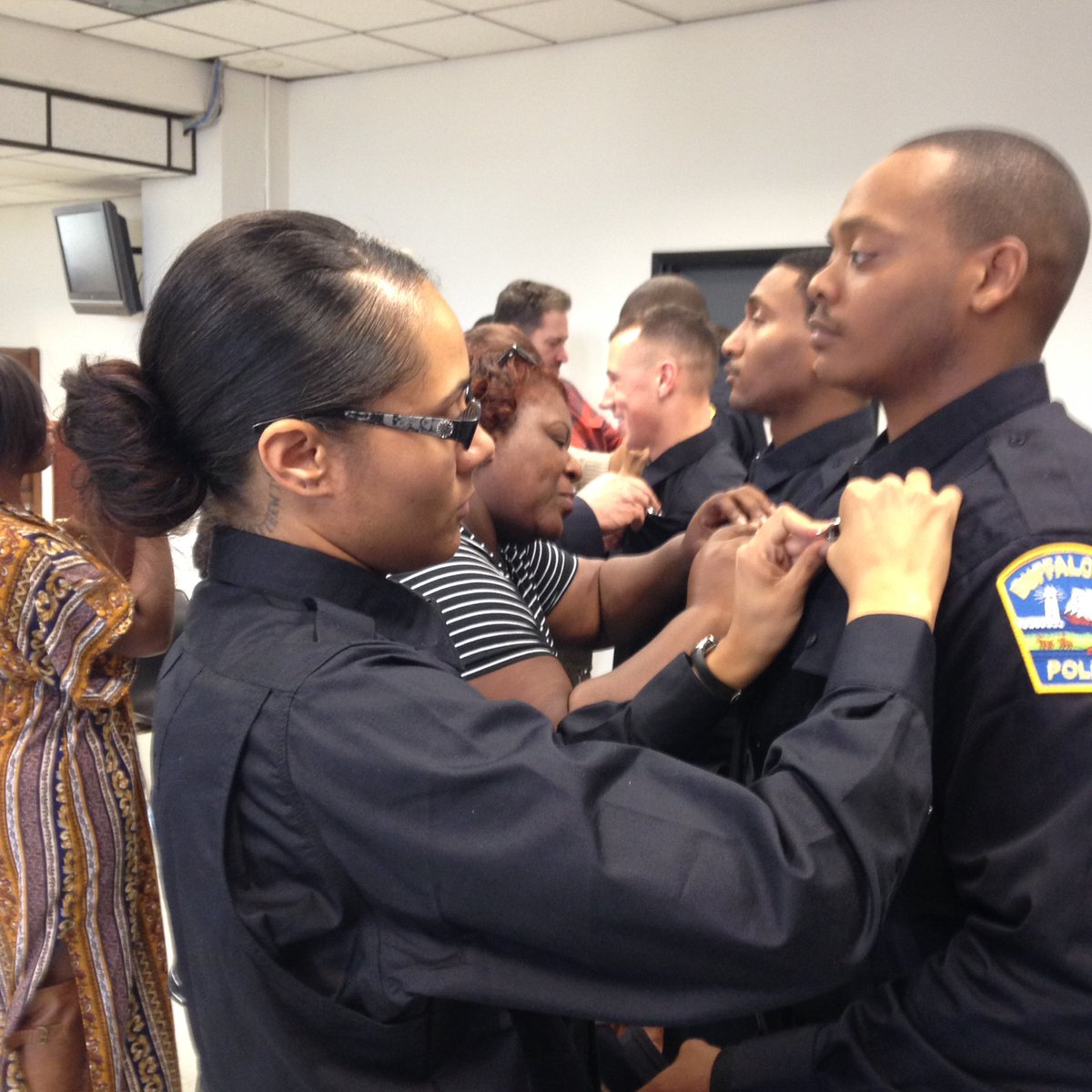Felisha Kenyon pins a badge on Christopher Bridgett during a ceremony in Buffalo Police Headquarters. (Lou Michel/News file photo)