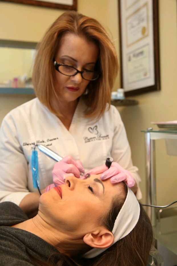 Sherry Hale, left, a state-certified and licensed dermal pigmentation and medical laser cosmologist, tattooed new eyebrows on Carla Lynch, who lost them during chemotherapy for breast cancer. (Sharon Cantillon/Buffalo News)