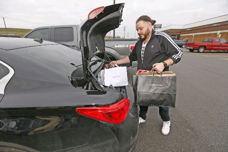 Arthur Yuro, of Toronto, fills his trunk with bags of gifts from the Fashion Outlets of Niagara Falls on Friday. (Robert Kirkham/Buffalo News)