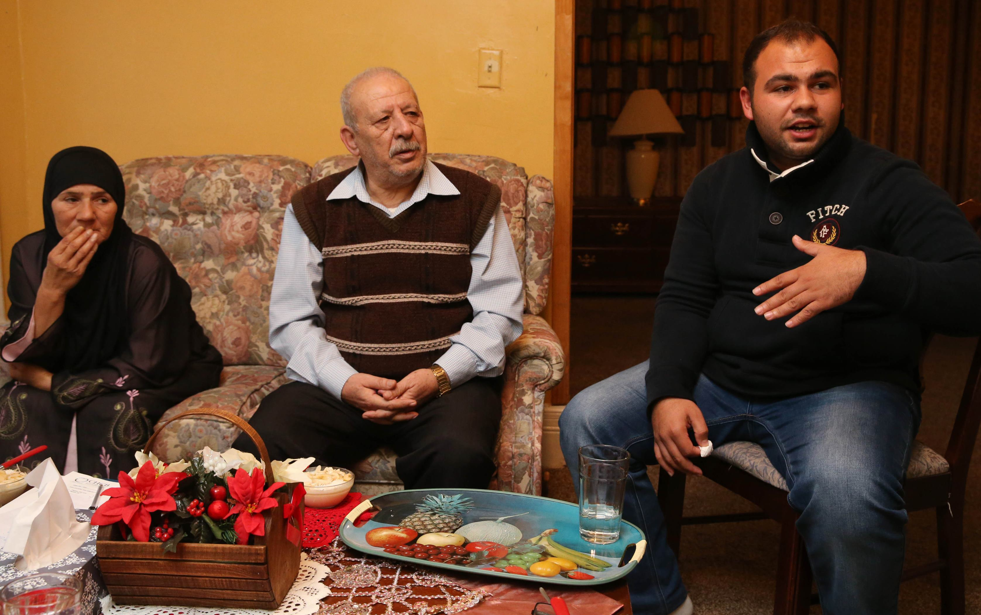 The Ay Toghlo family, refugees from Syria, are now residents on Buffalo's West side. Photo taken in their home, Wednesday, Nov. 23, 2016. From left are Eidah Al Suleiman, 54, her husband Mohammed Ay Toghlo, 67, and their son Najati Ay Toghlo, 24. They talk about how they came to the United States and how happy they are to be here. Husband and wife arrived on August 24 and their son arrived on Spetember 21.(Sharon Cantillon/Buffalo News)