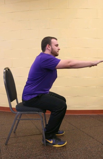 YMCA personal trainer Tom Prendergast demonstrates a chair squat.