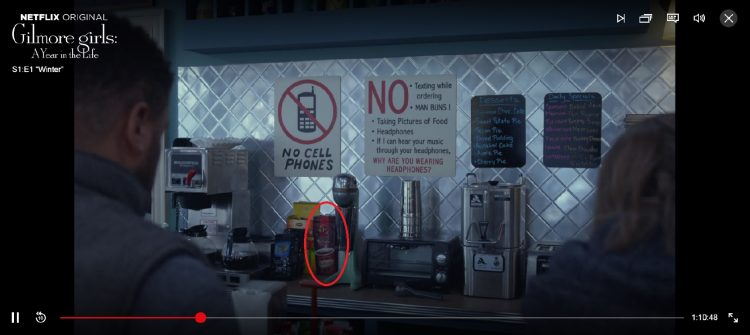 "A screenshot of a still frame in Netflix's ""Gilmore Girls: A Year in the Life."" A Tim Hortons original blend ground coffee bag is circled in red next to a box of Lipton tea."