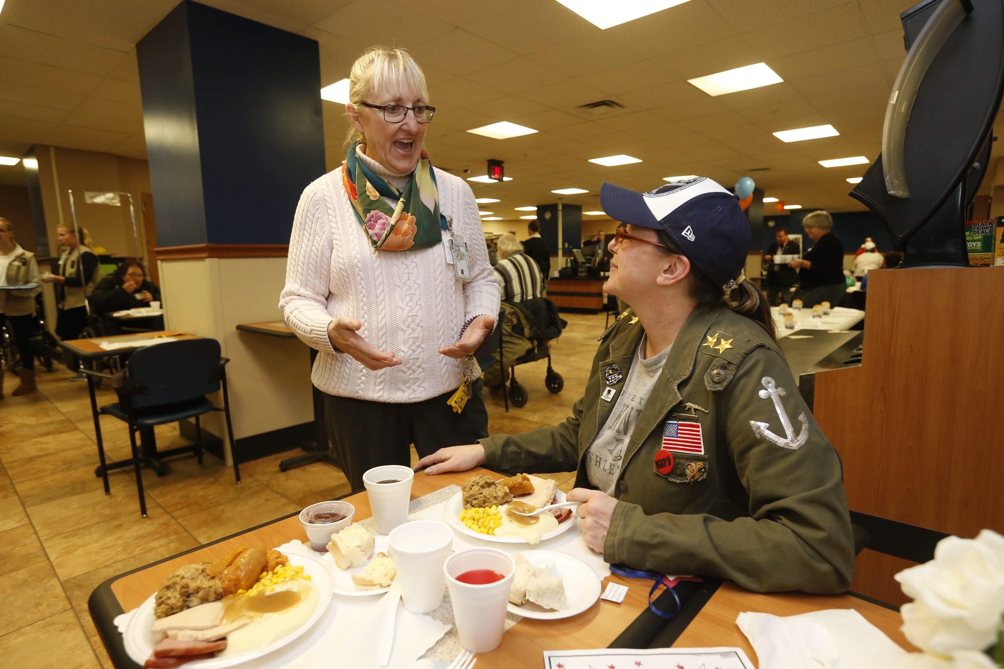 Judith Kaczmarek visits with Elizabeth Demler, a Navy veteran, right, during a Thanksgiving dinner in the cafeteria of the VA Hospital last November. (Robert Kirkham/Buffalo News file photo)