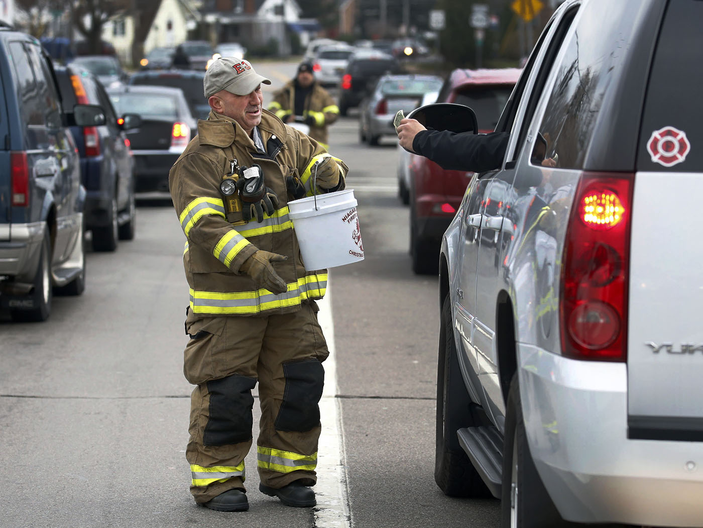 Mike Perri, a 26 year veteran of the City of Niagara Falls, NY fire department, solicits donations to their annual toy and food drive for the needy at the intersection of Niagara Falls Blvd. and Military in Niagara Falls, NY onFriday, Nov. 25, 2016. (Robert Kirkham/Buffalo News)