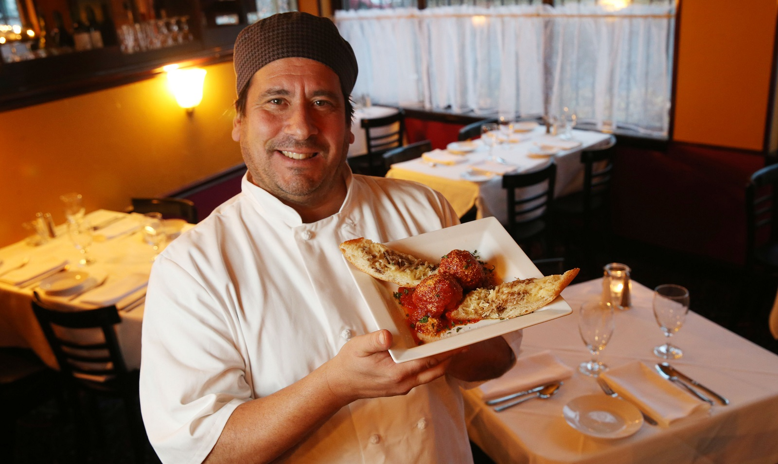 Bellini's Bistro owner and chef Mike Navarro presents the tomato braise polpette. (Sharon Cantillon/Buffalo News)