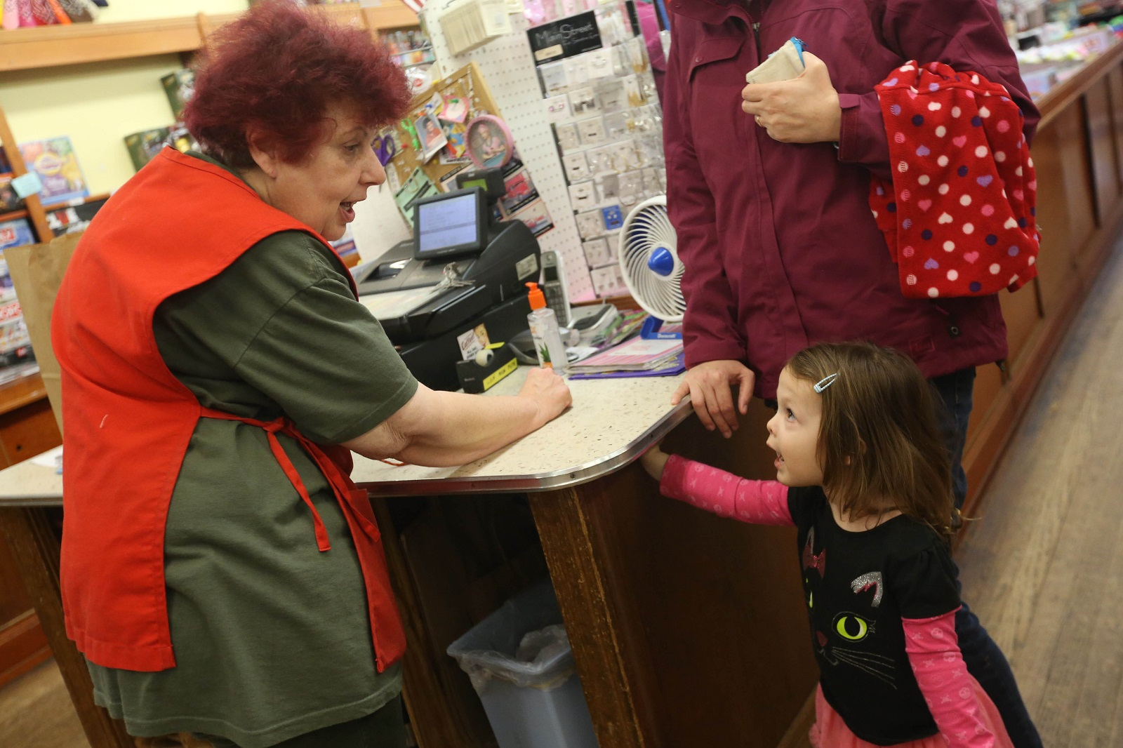 Clerk Sue Yoerk, left, listens to Lily Deriso, 2, of Strykersville, who has a lot to say. Behind Lily is her mom, Kate Deriso. (Sharon Cantillon/Buffalo News)