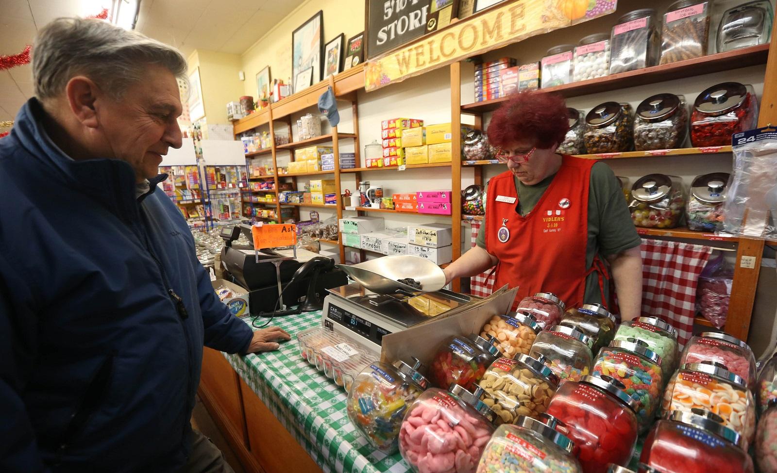 Clerk Sue Yoerk serves customer Dennis Caldwell, of Hamburg, at the candy counter. (Sharon Cantillon/Buffalo News)