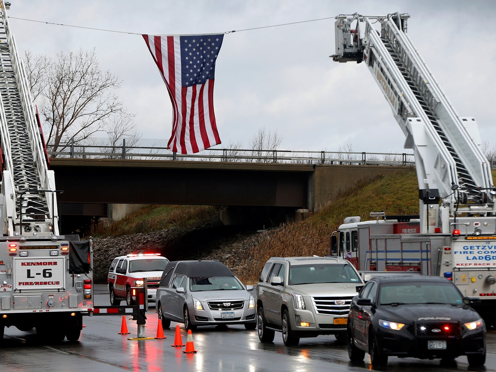 The funeral procession of Kenmore Police Officer Joshua Davidson drives past the American flag in Amherst Thursday, December 1, 2016.    (Mark Mulville/The Buffalo News)
