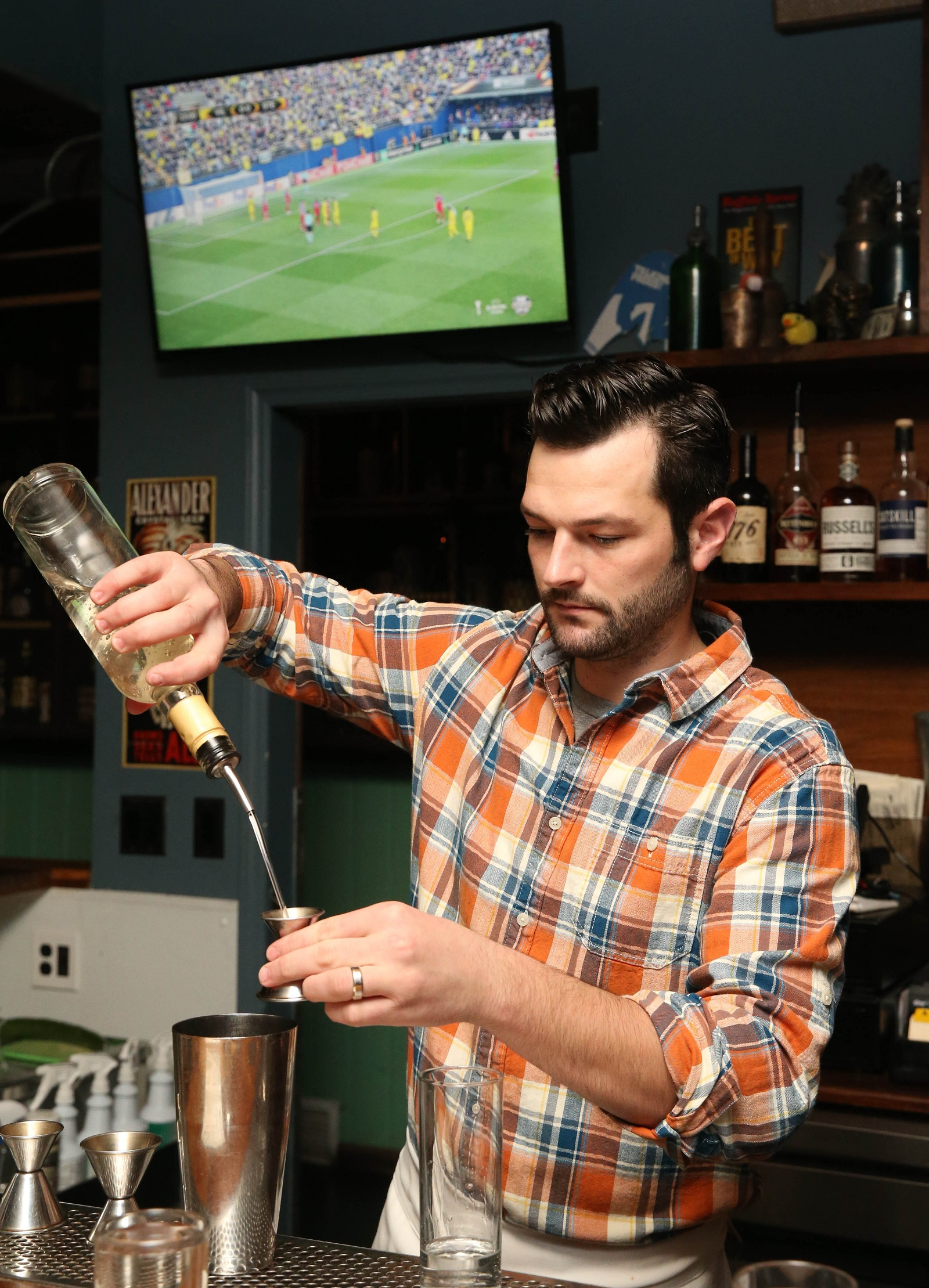 Ballyhoo bar manager Frank Pusateri makes a drink while a soccer game is being played on the TVs. (Sharon Cantillon/Buffalo News)